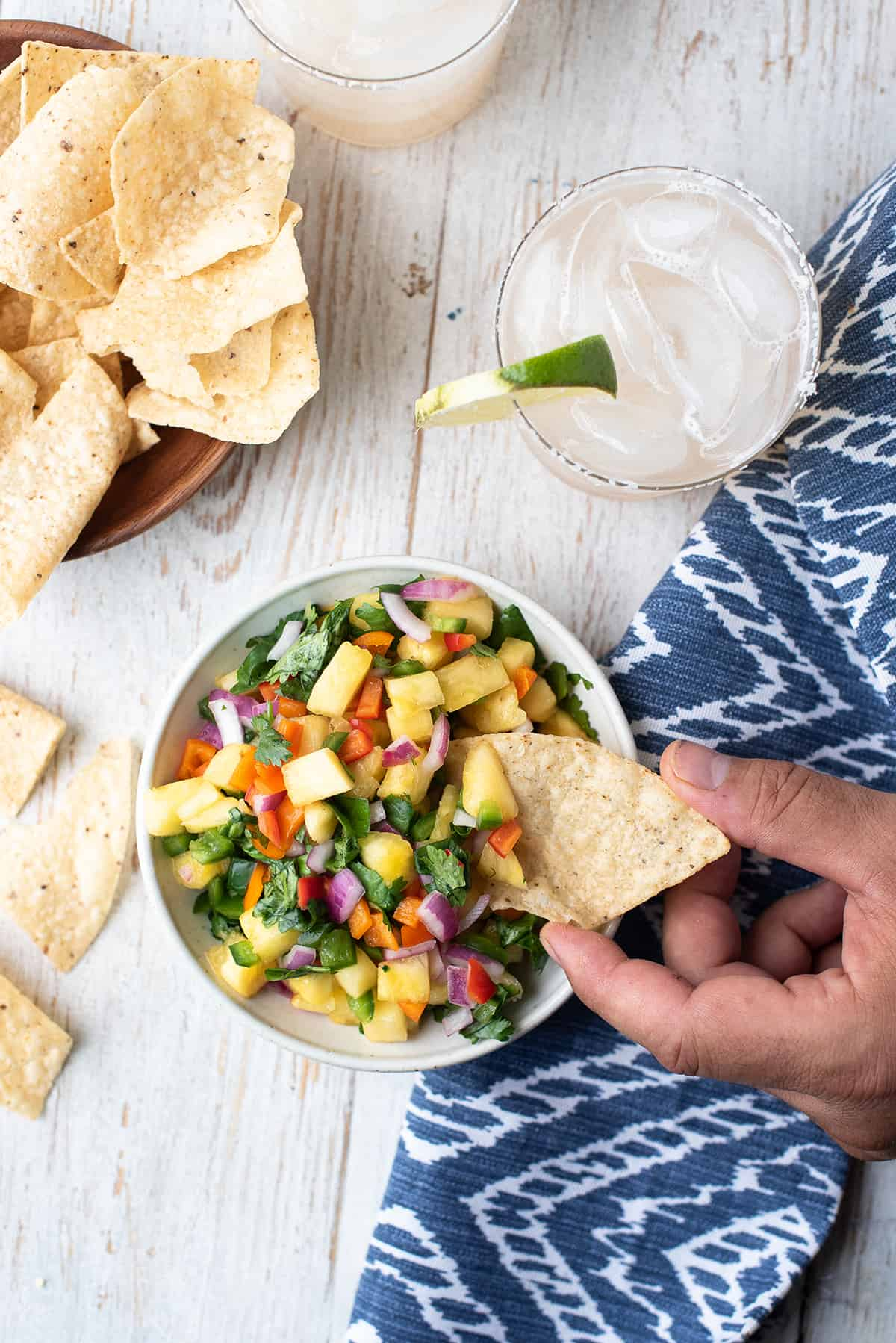 hand holding tortilla chip with pineapple salsa