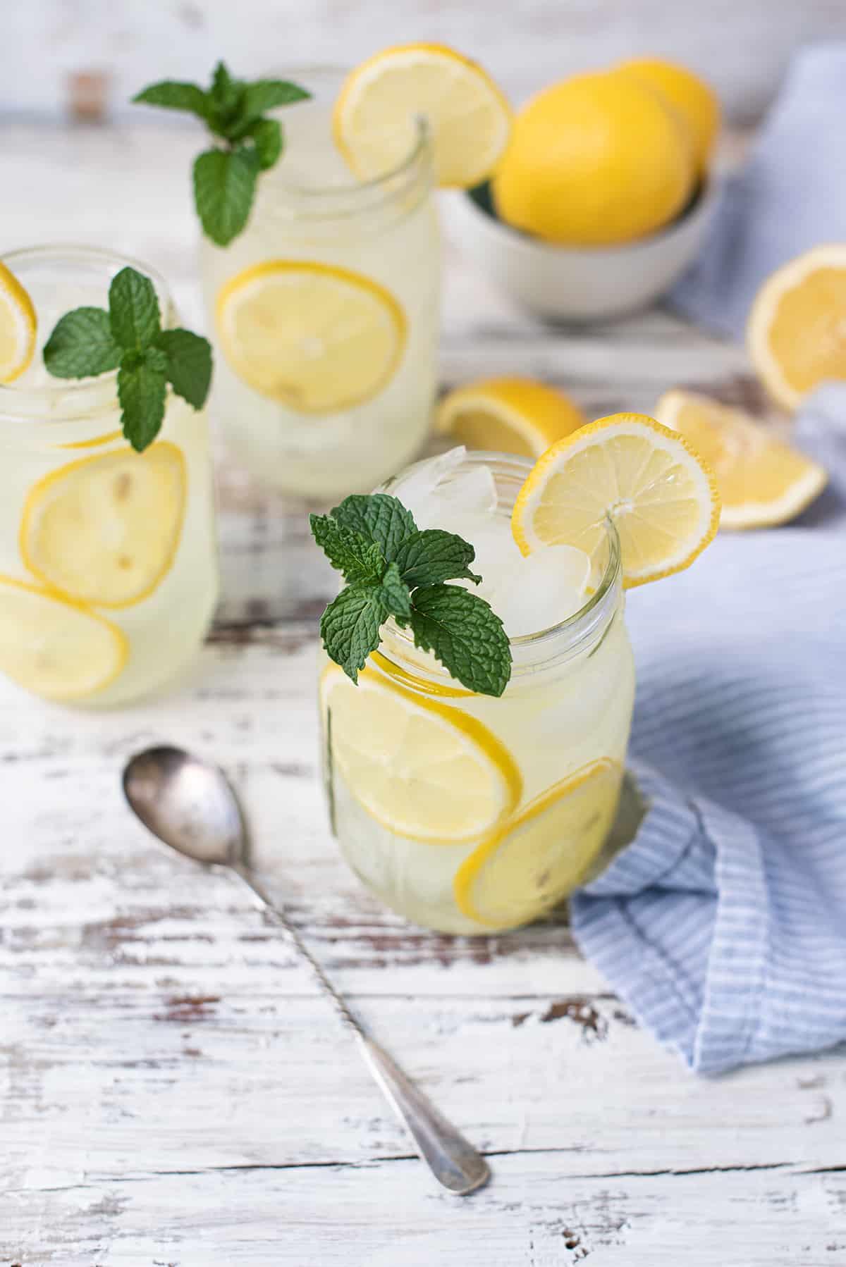 lemonade in mason jars with mint garnish and fresh lemons on white wooden table