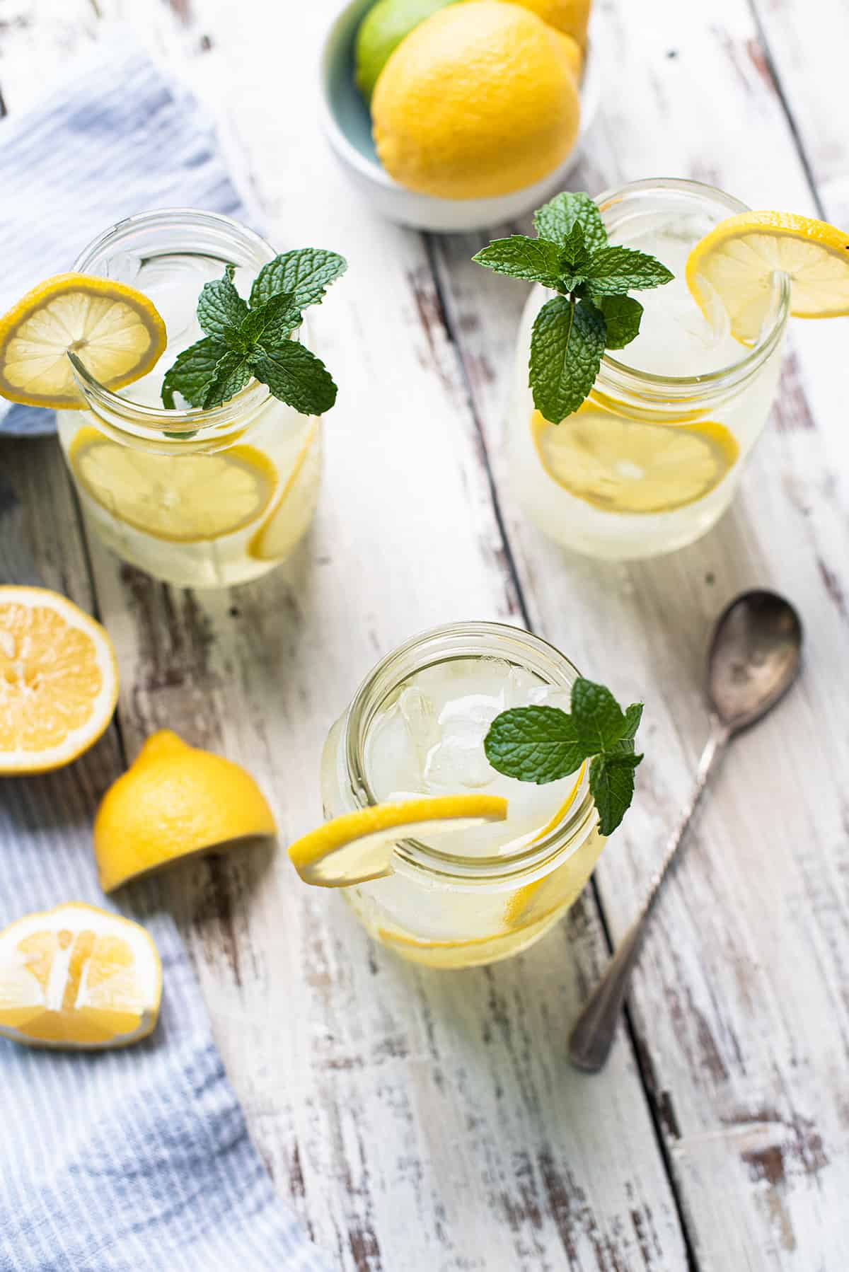 lemonade in mason jars with mixing spoon on white wooden table