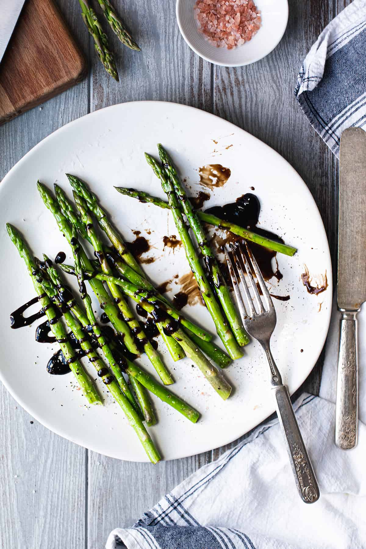 messy asparagus on plate with balsamic reduction and fork