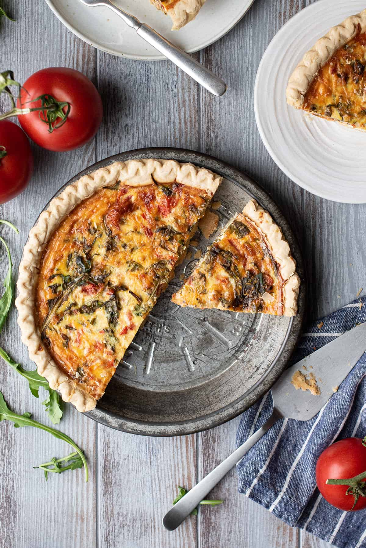 roasted tomato & arugula quiche, sliced in pan with serving piece