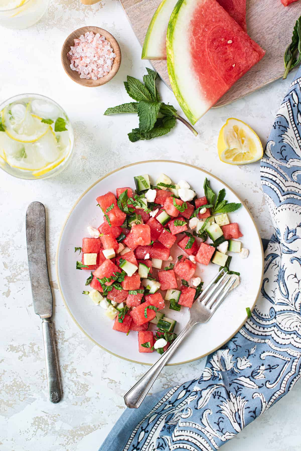 chopped watermelon salad on white plate with fork, knife, and blue patterned napkin