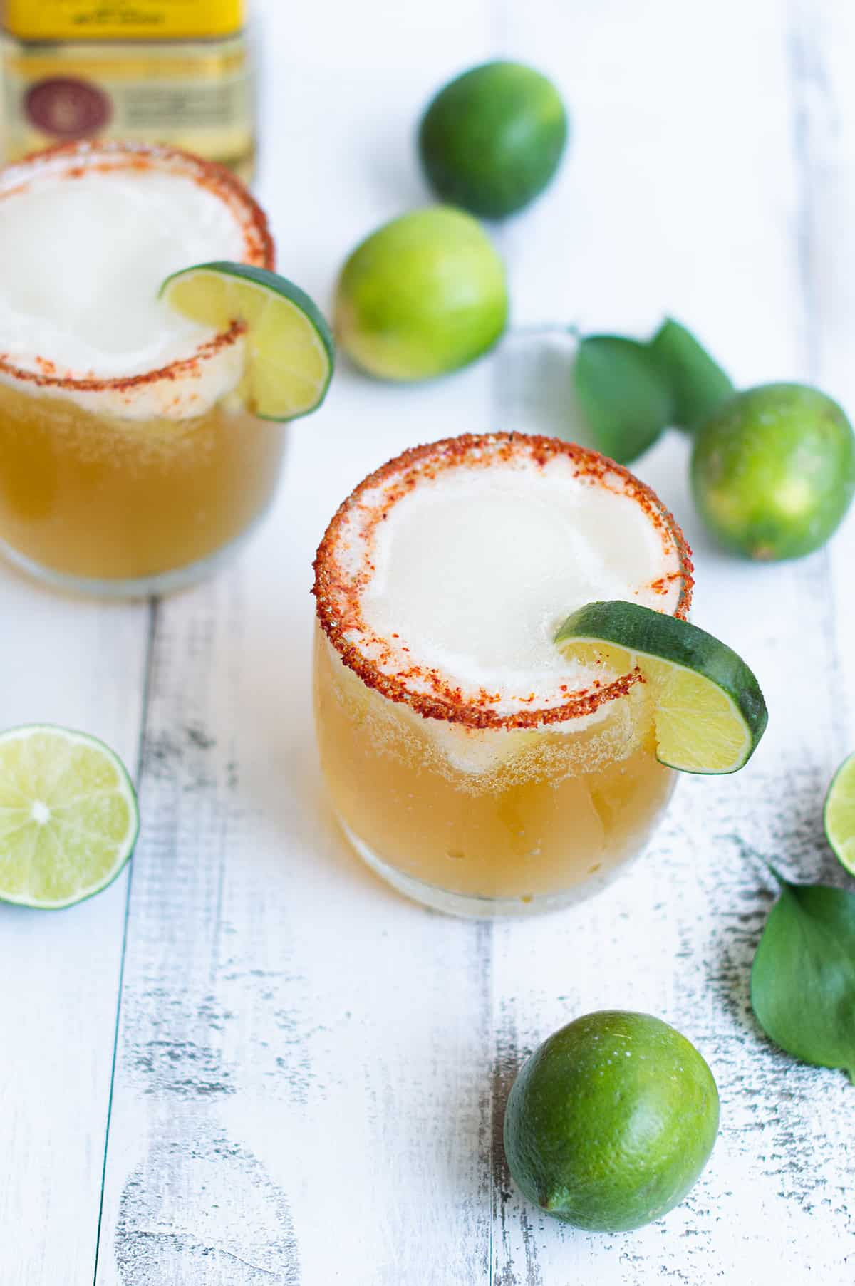 beer margarita, garnished with lime and chili salt, on white table with limes