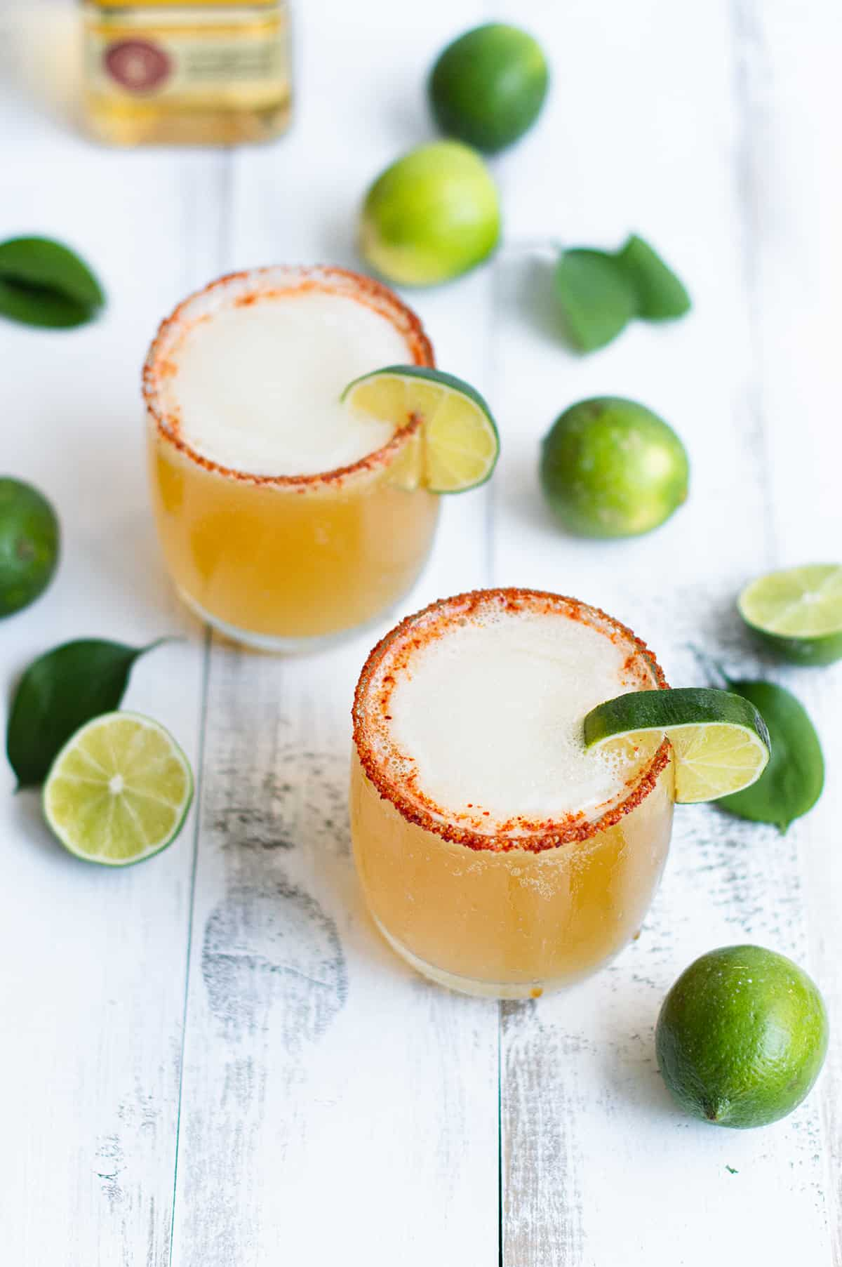 two beer margaritas garnished with lime and chili salted rim on white table
