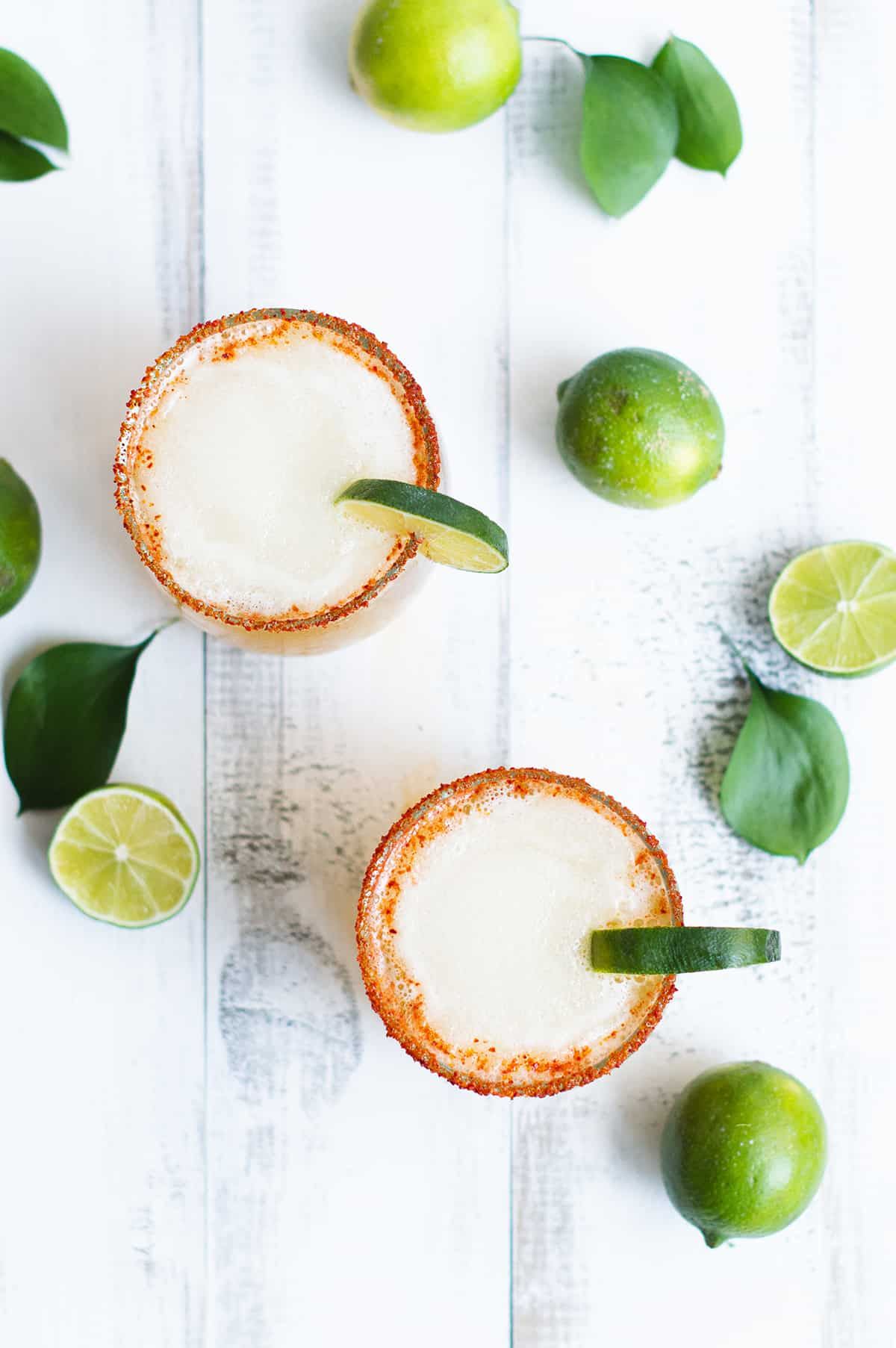 two beer margaritas, garnished with lime and chili salt on white table with limes