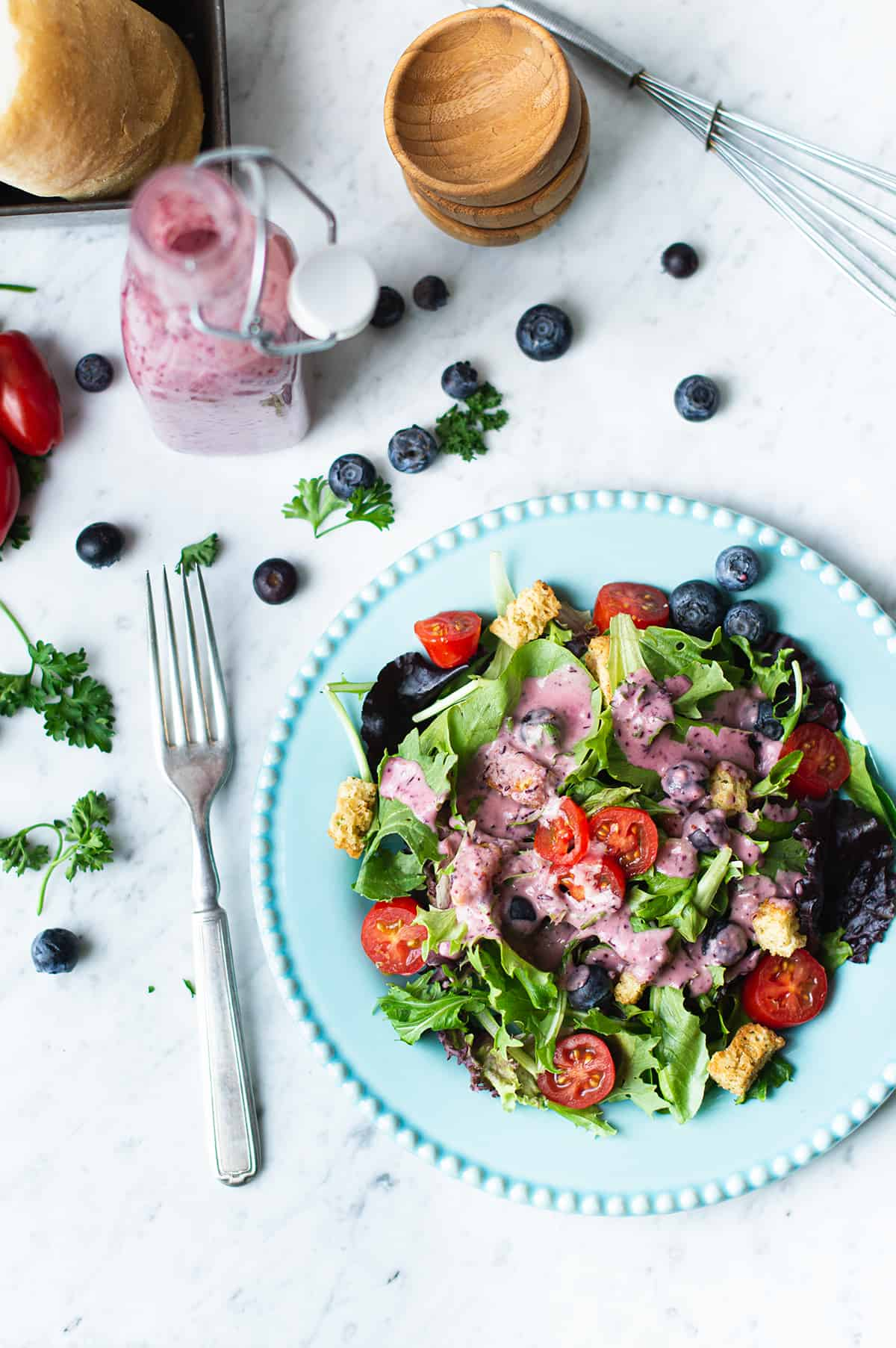 mixed greens drizzled with blueberry vinaigrette on a blue plate with fork