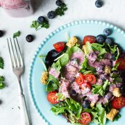 mixed green drizzled with blueberry vinaigrette on blue plate