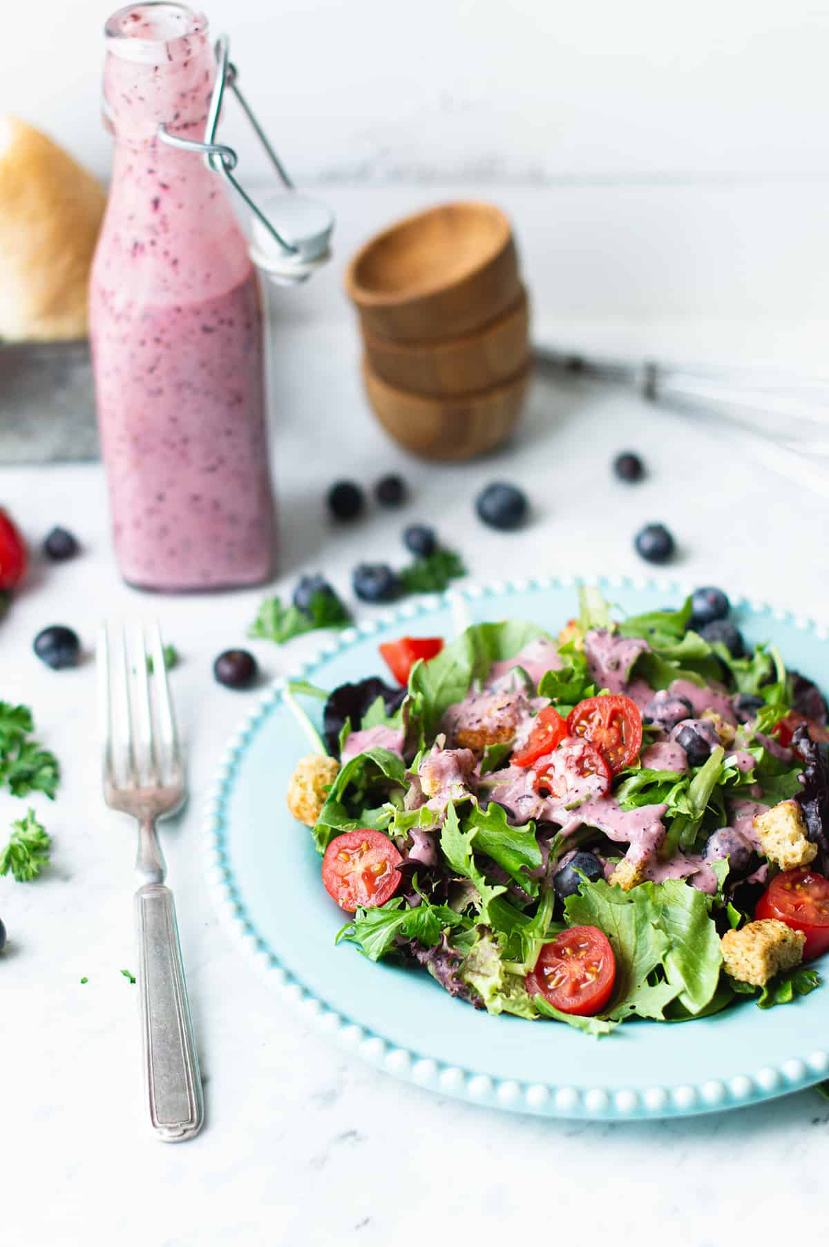 blueberry vinaigrette poured over mixed greens on blue plate with fork