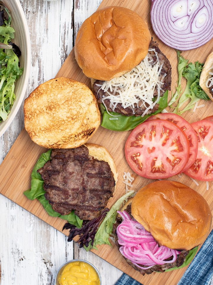 burgers on platter with toppings