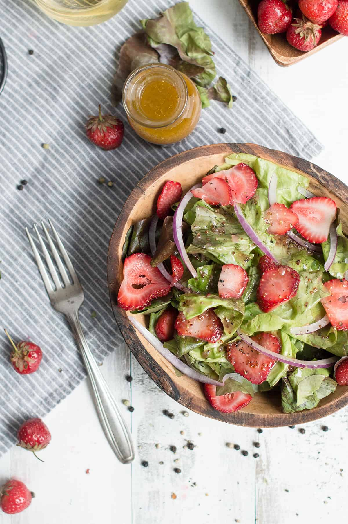 strawberry salad in wooden bowl + fork