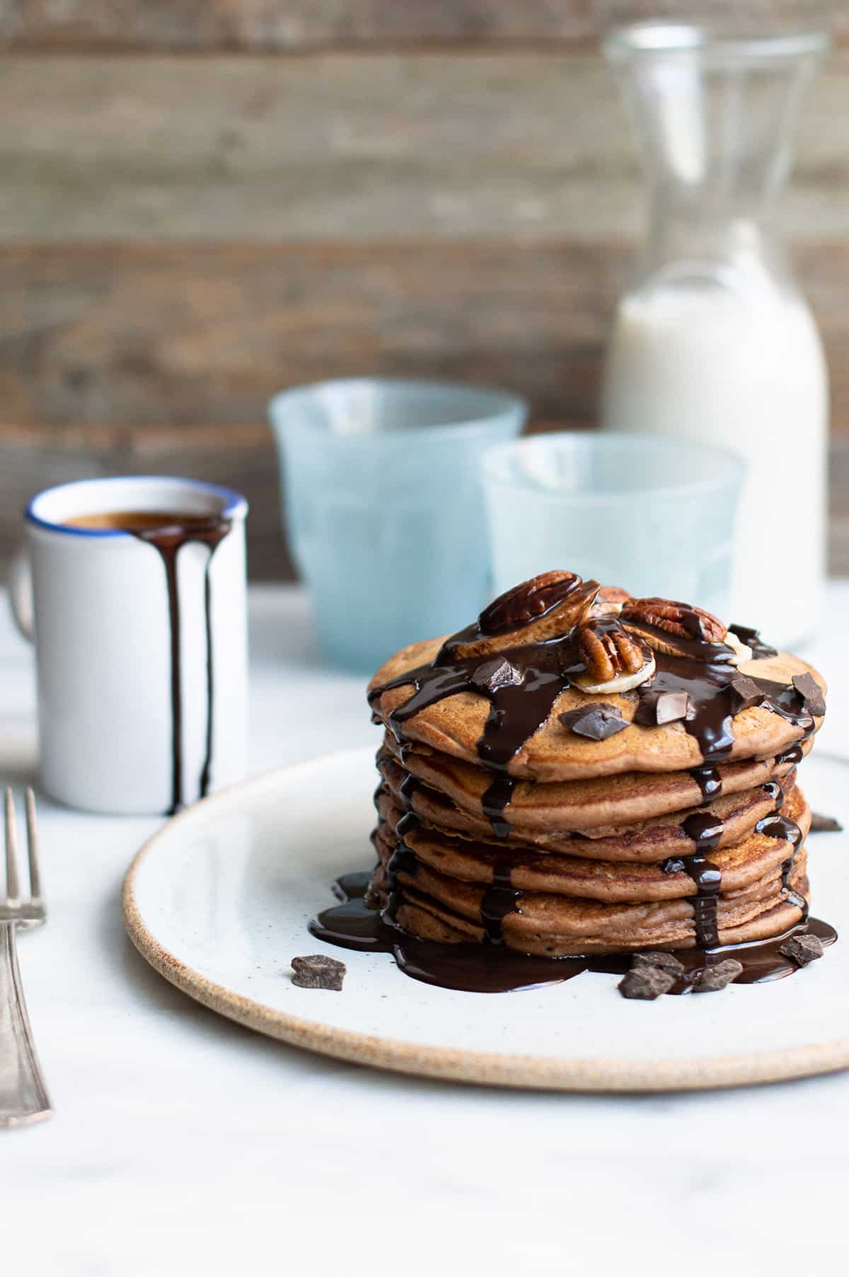 stack of triple chocolate banana pancakes with chocolate syrup drizzle