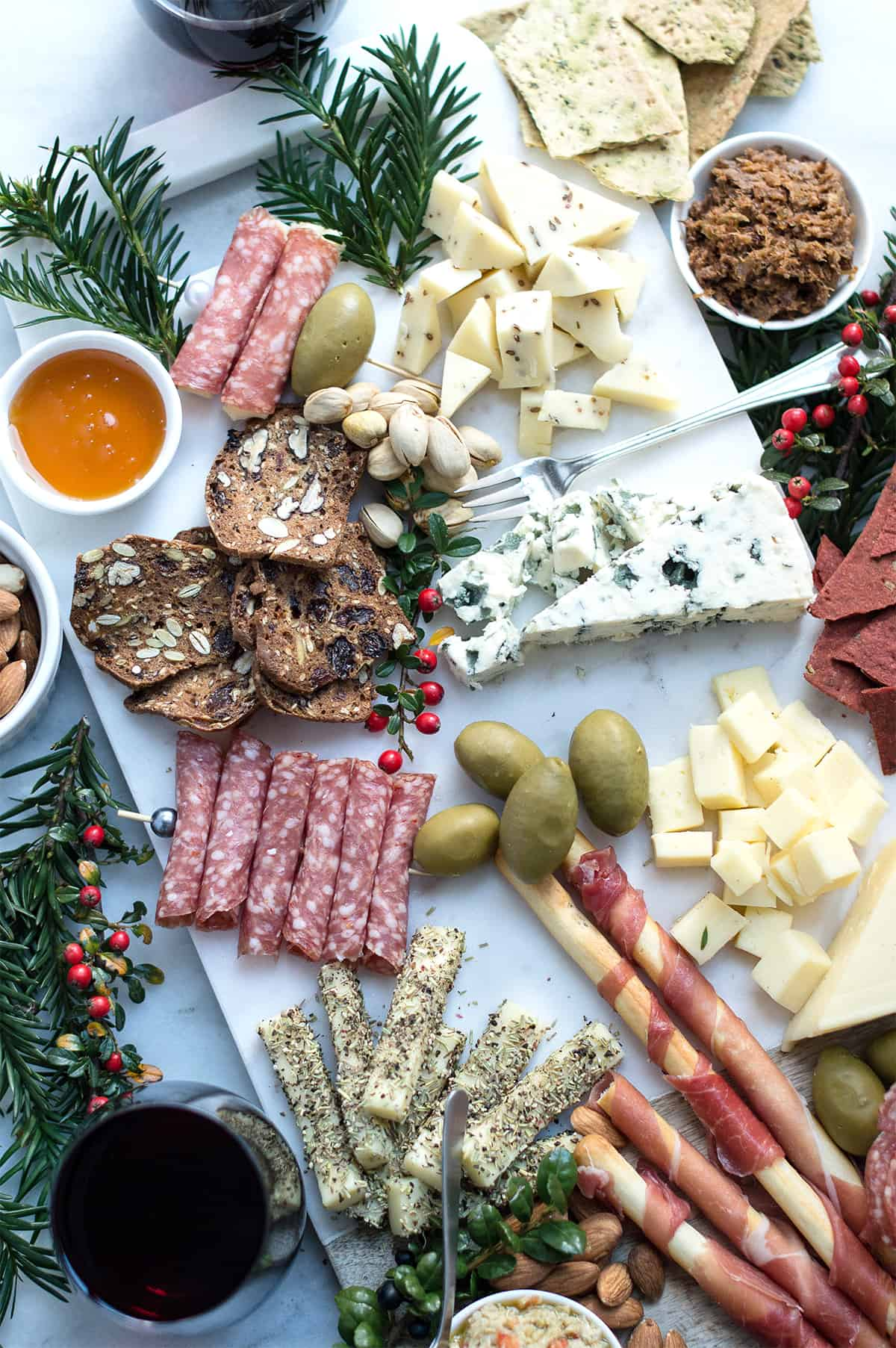 holiday cheese board with cold cuts, crackers, cheeses, and holiday garland