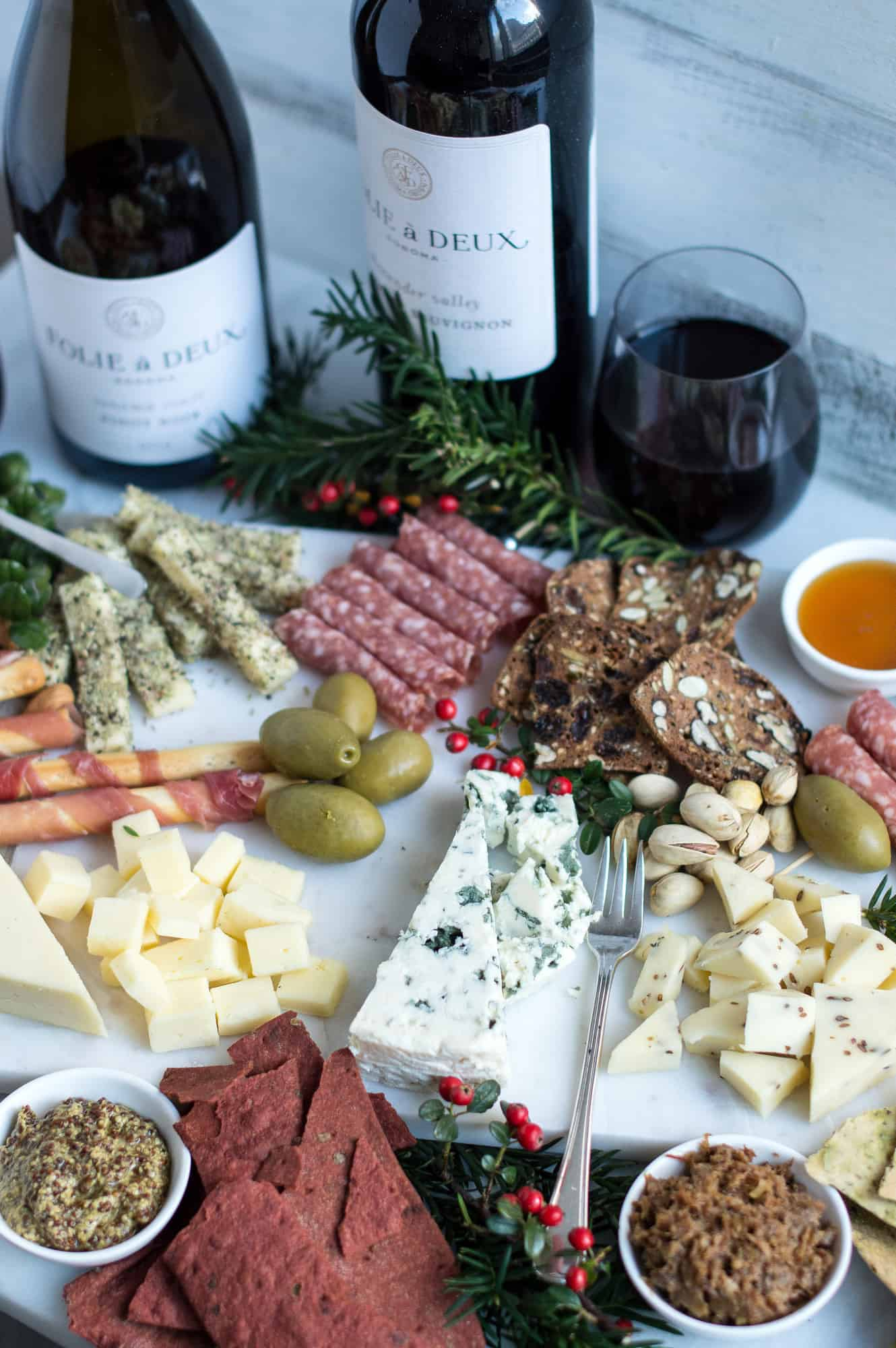 holiday cheese board with red wine and holiday garland