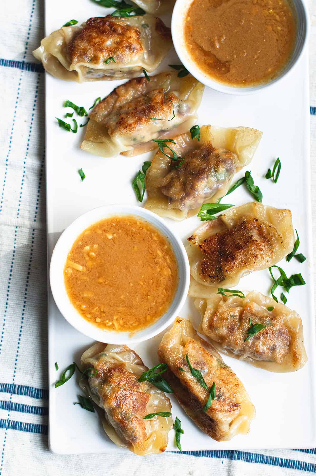thai chicken dumplings on white plate with bowl of peanut dipping sauce