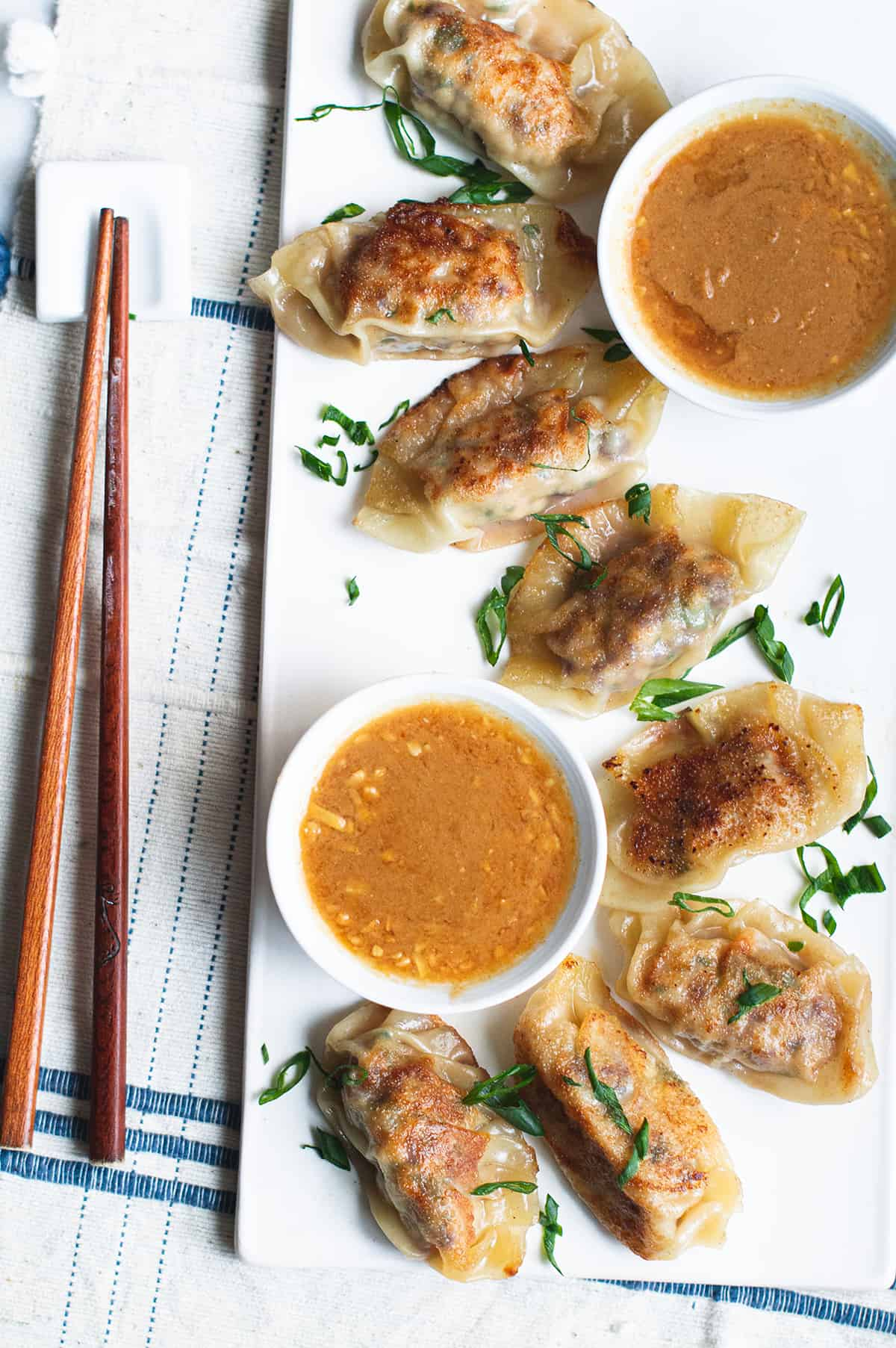 dumplings on a white plate with bowl of peanut dipping sauce