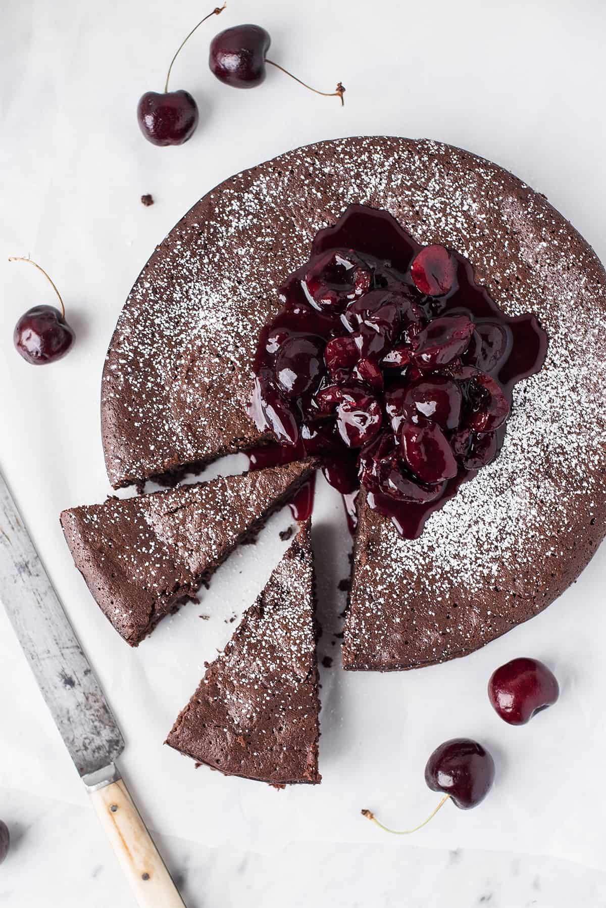 dark chocolate torte with bing cherry compote, sliced with knife