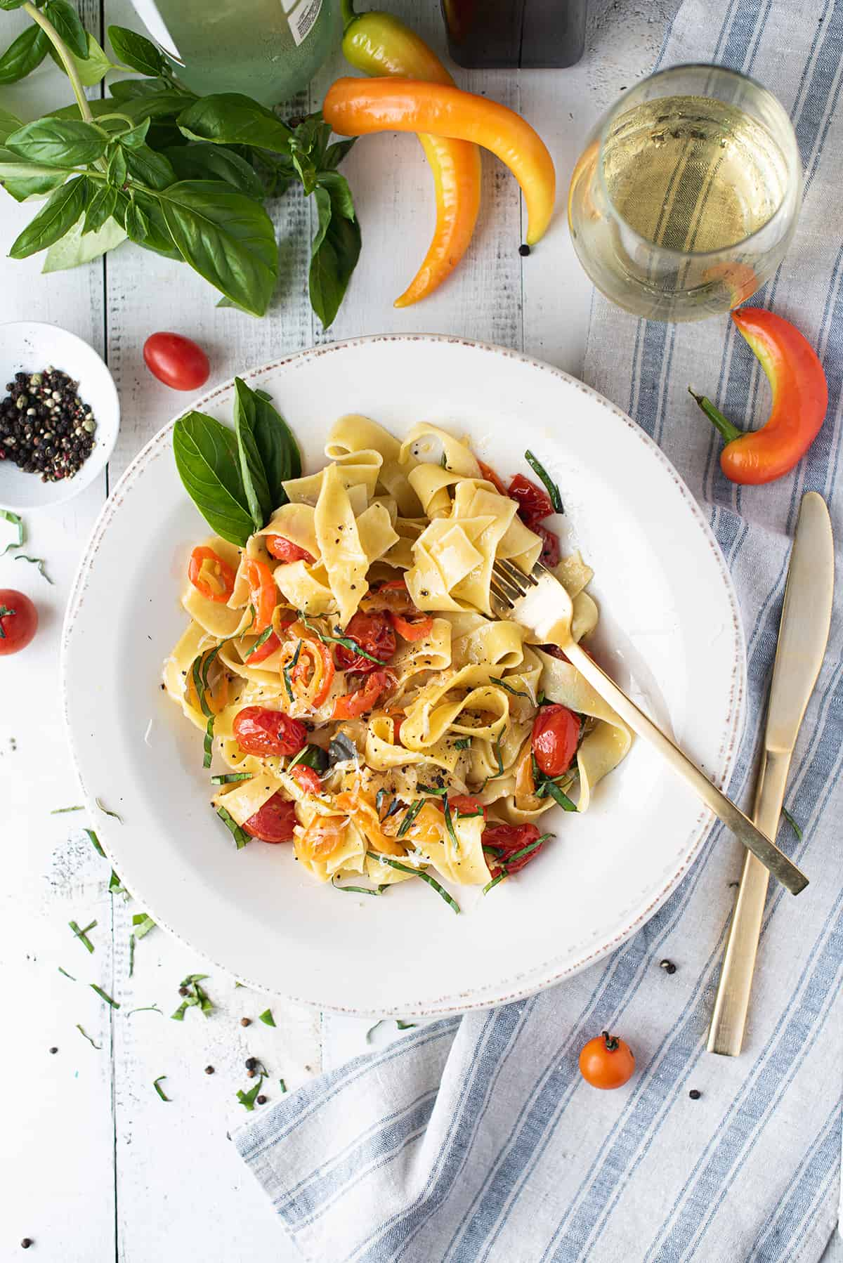 white bowl of pappardelle with tomatoes, peppers, basil on white table with blue napkin