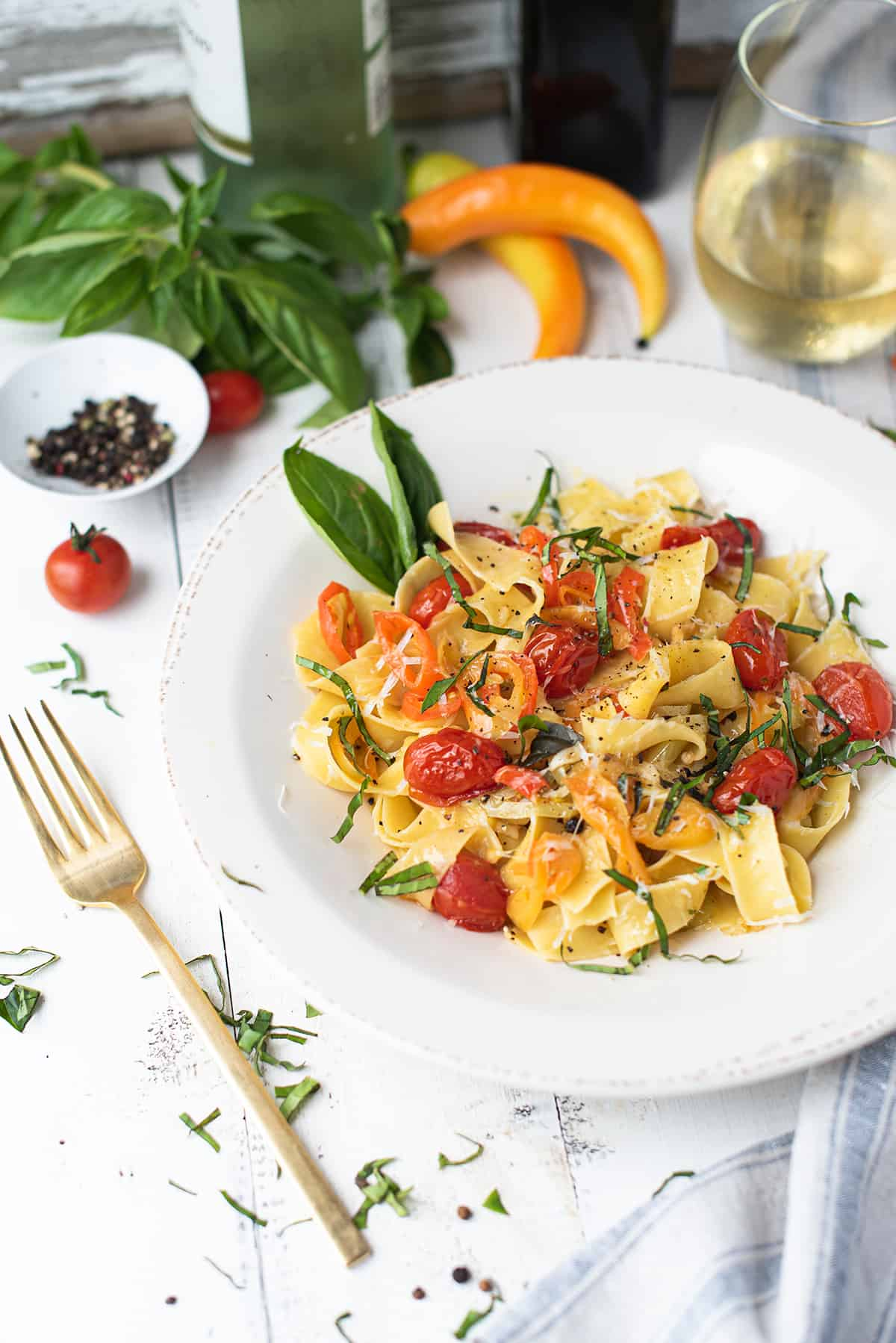 bowl of pappardelle with tomatoes, pepper, basil, on white table with gold fork