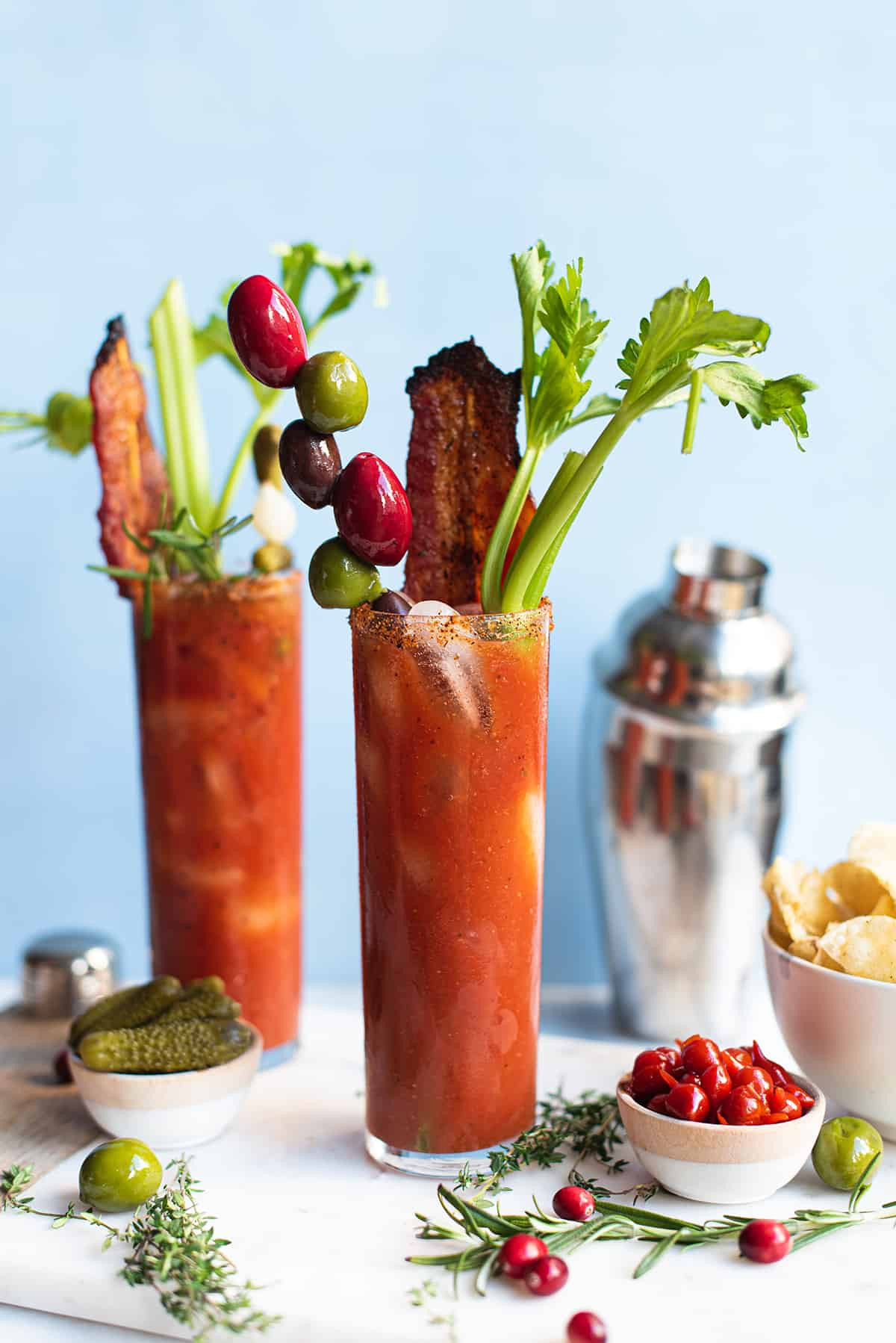 Bacon Bloody Mary in tall glass, garnished with celery, olives on blue background