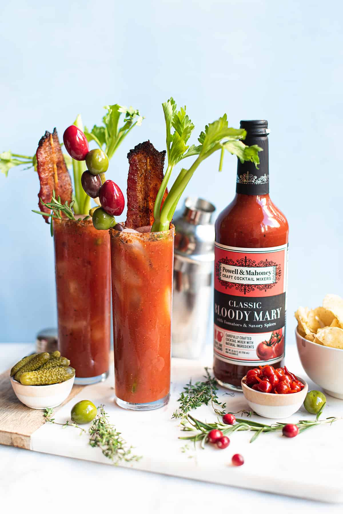 2 Bacon Bloody Marys in tall glasses, garnished with celery, olives + Bloody Mary mix on blue background