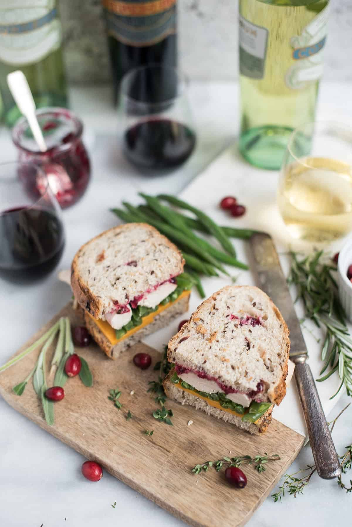 turkey sandwich cut in half on board with knife and red wine