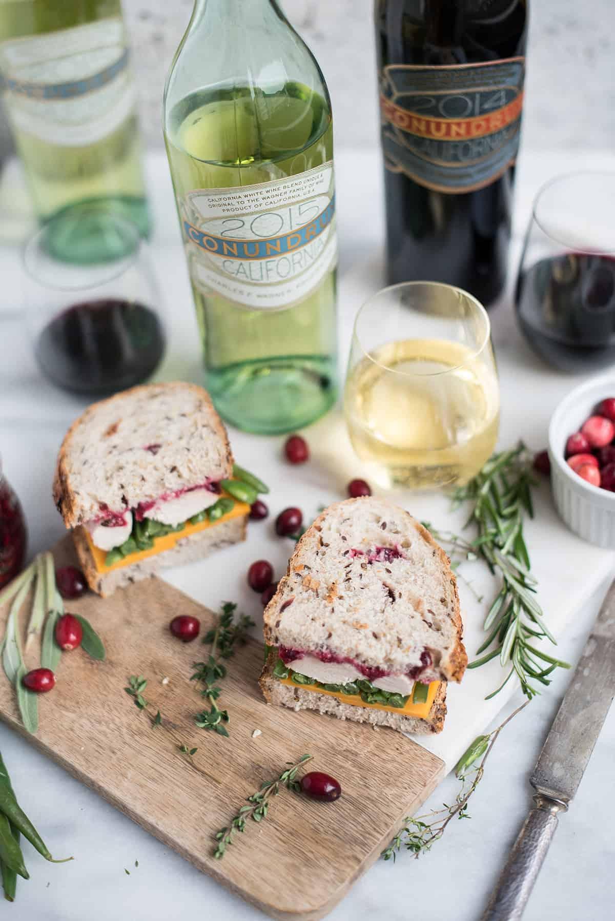 leftover turkey sandwich cut in half on board with white wine