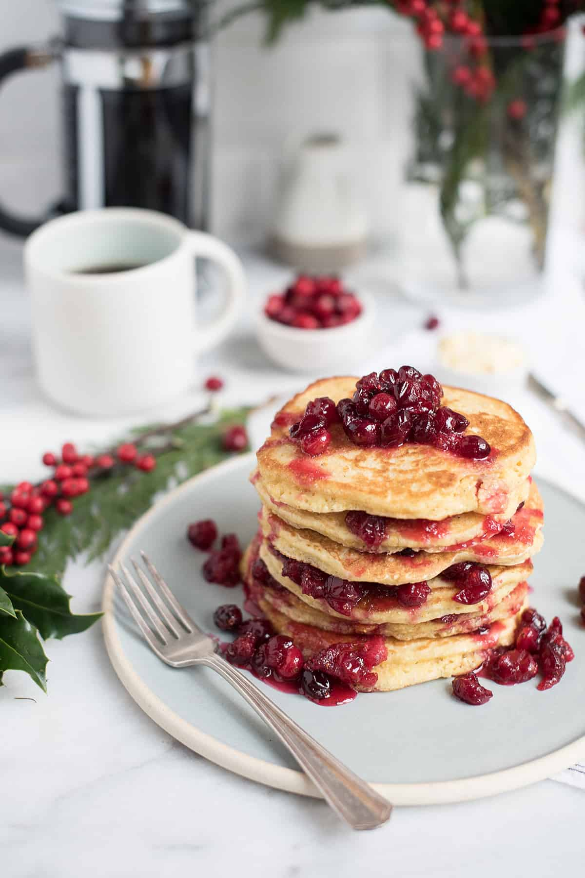 stack of cornmeal griddle cakes with cranberry compote on table with coffee