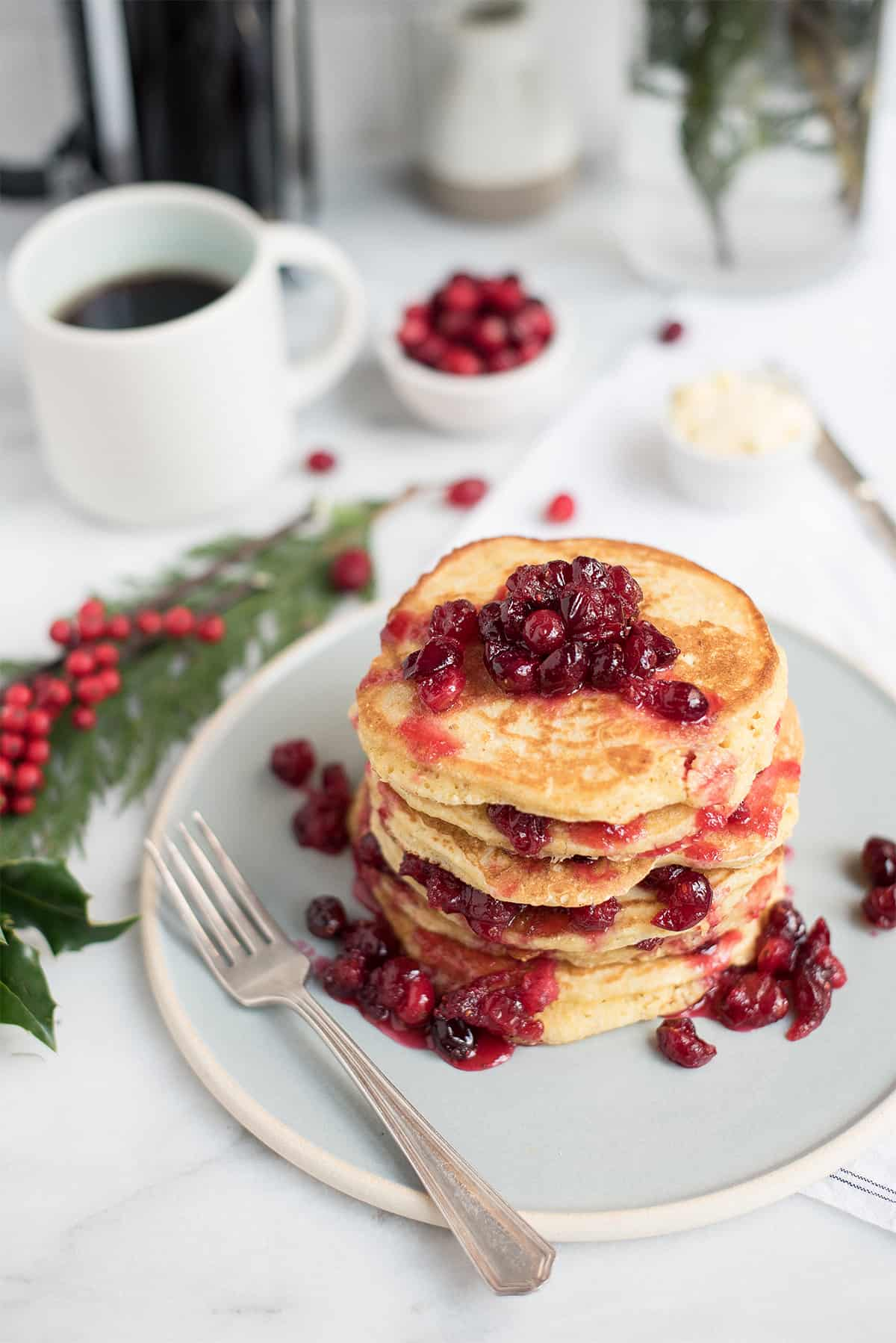 stack of cornmeal griddle cakes with cranberry compote with coffee & holiday garland