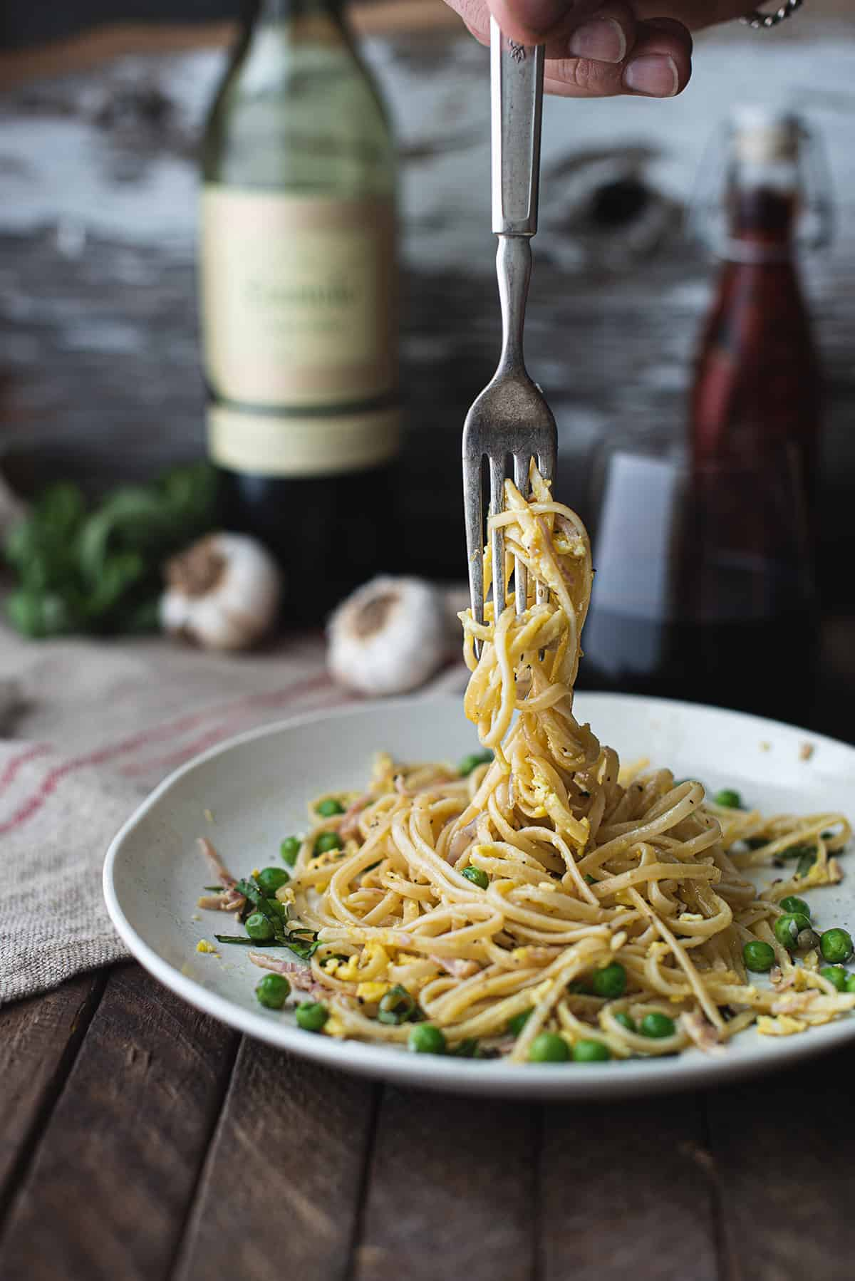 fork twisting classic pasta carbonara above plate