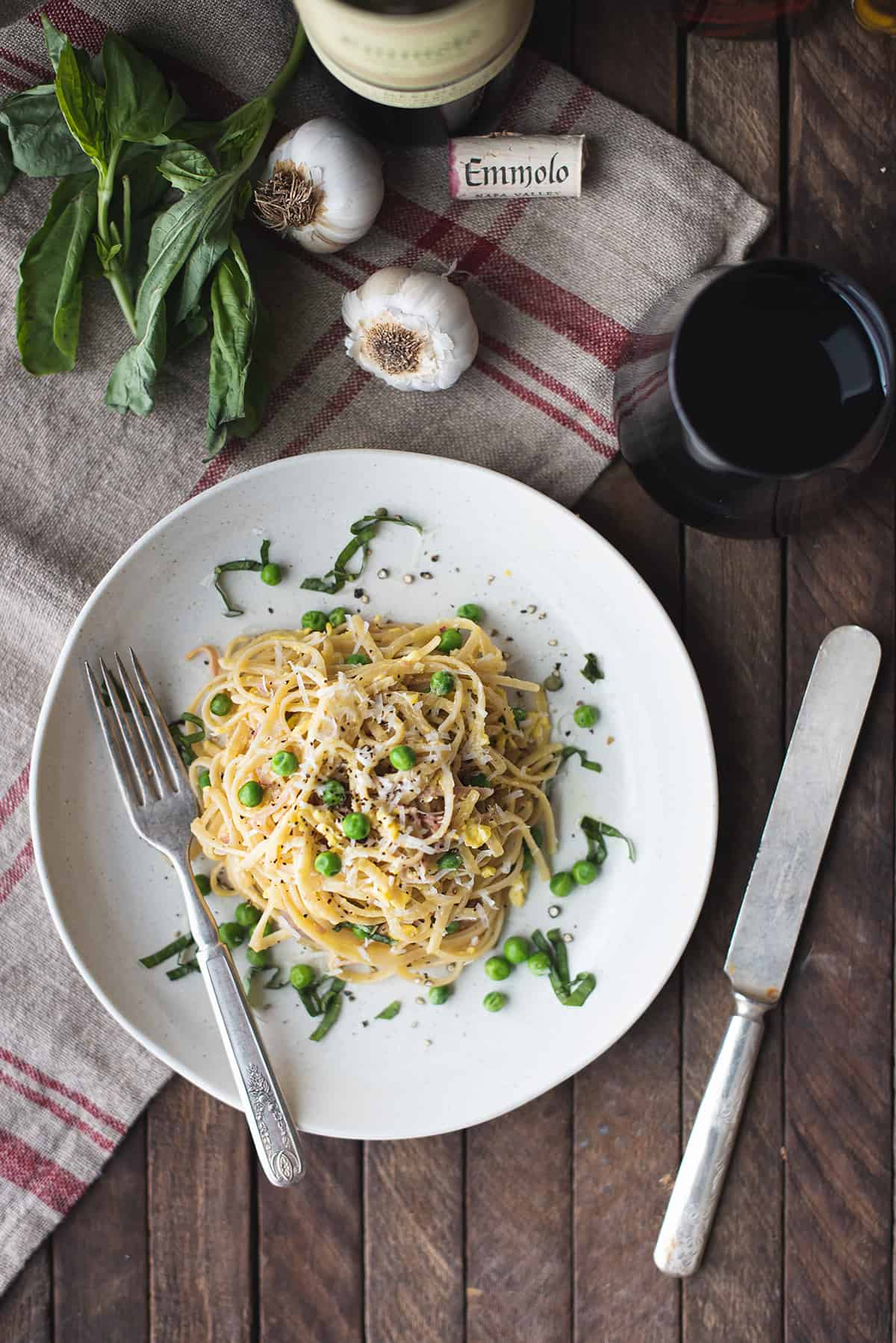 plate of classic pasta carbonara with fork and knife