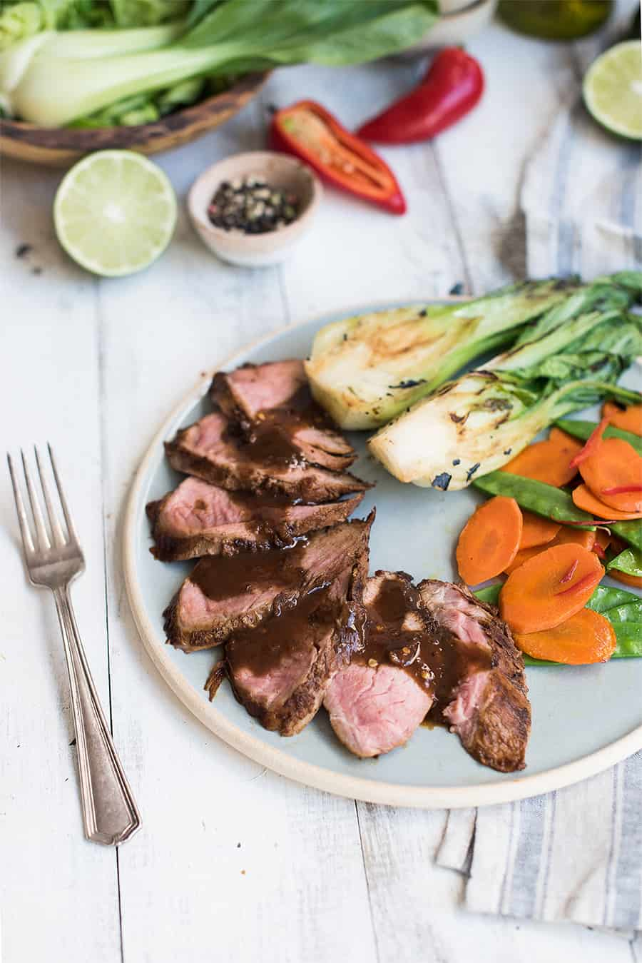 five spice sticky pork tenderloin, sliced on plate with veggies
