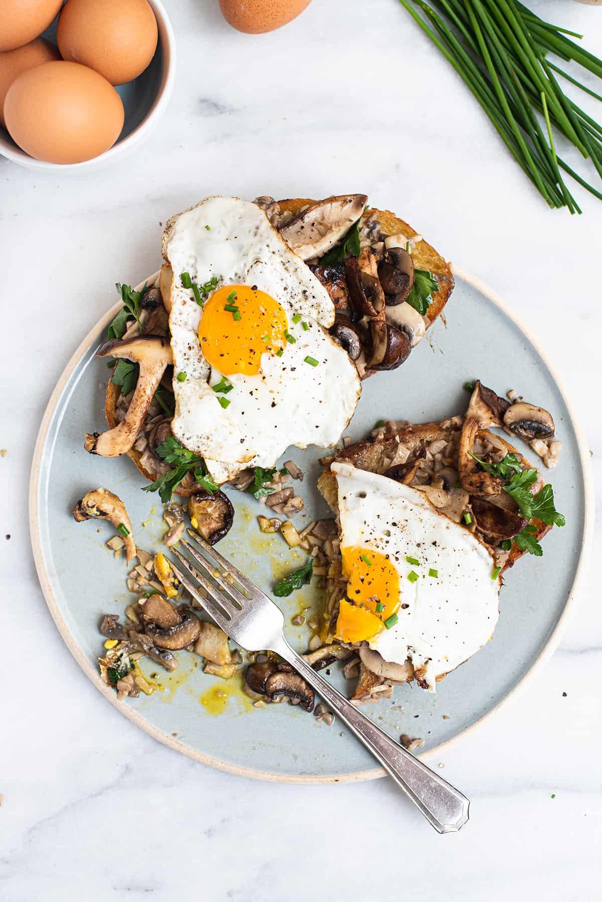 half eaten mushroom toasts on blue plate with fork