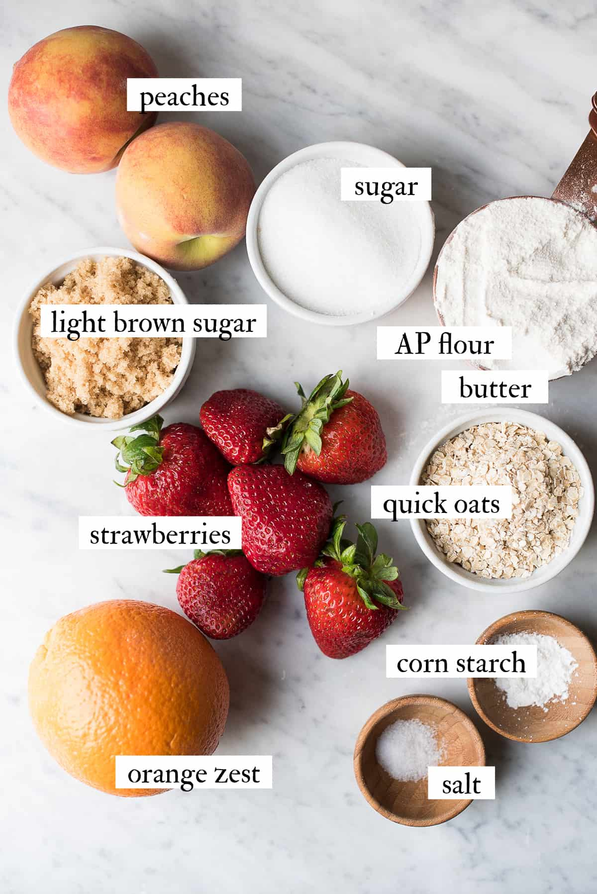 ingredients for strawberry peach crumble on white marble surface