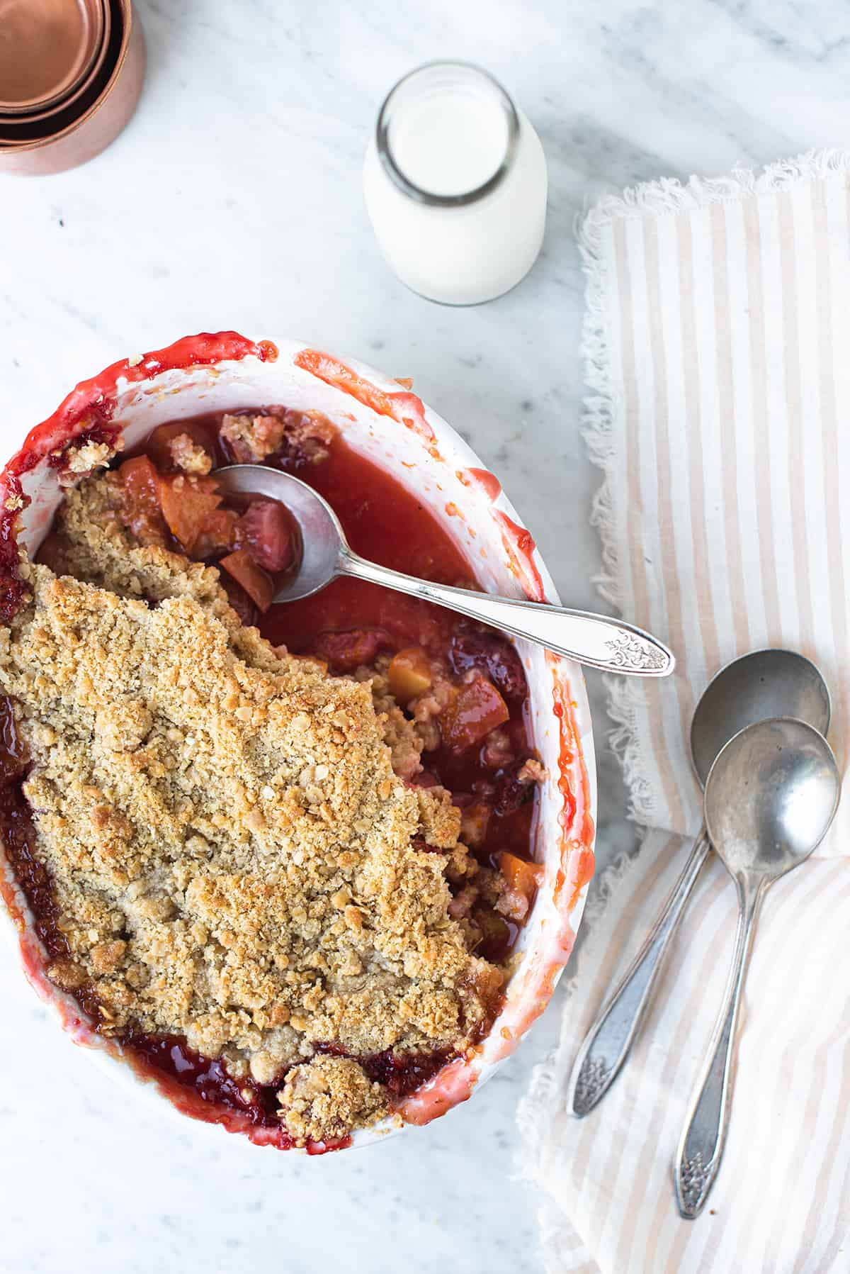 fruit crumble in white baking dish, some scooped out with serving spoons + pink striped napkin