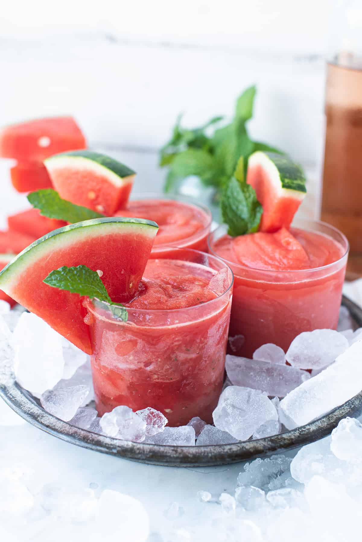 close up of glasses of watermelon frosé in pan of ice