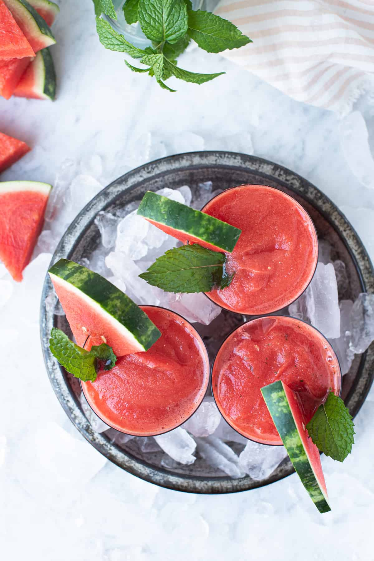 three glasses of watermelon frosé in pan of ice garnished with watermelon triangles