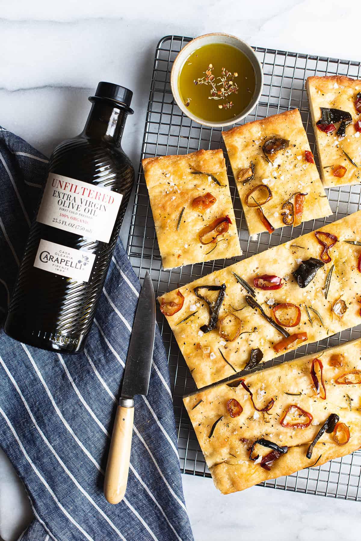 pepper focaccia, sliced on baking rack with bottle of Carapelli Olive Oil