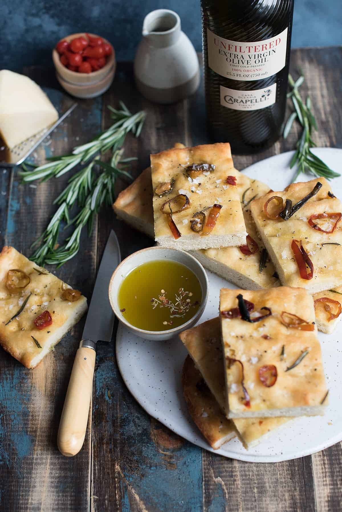 sliced pepper focaccia with knife and rosemary on white serving board