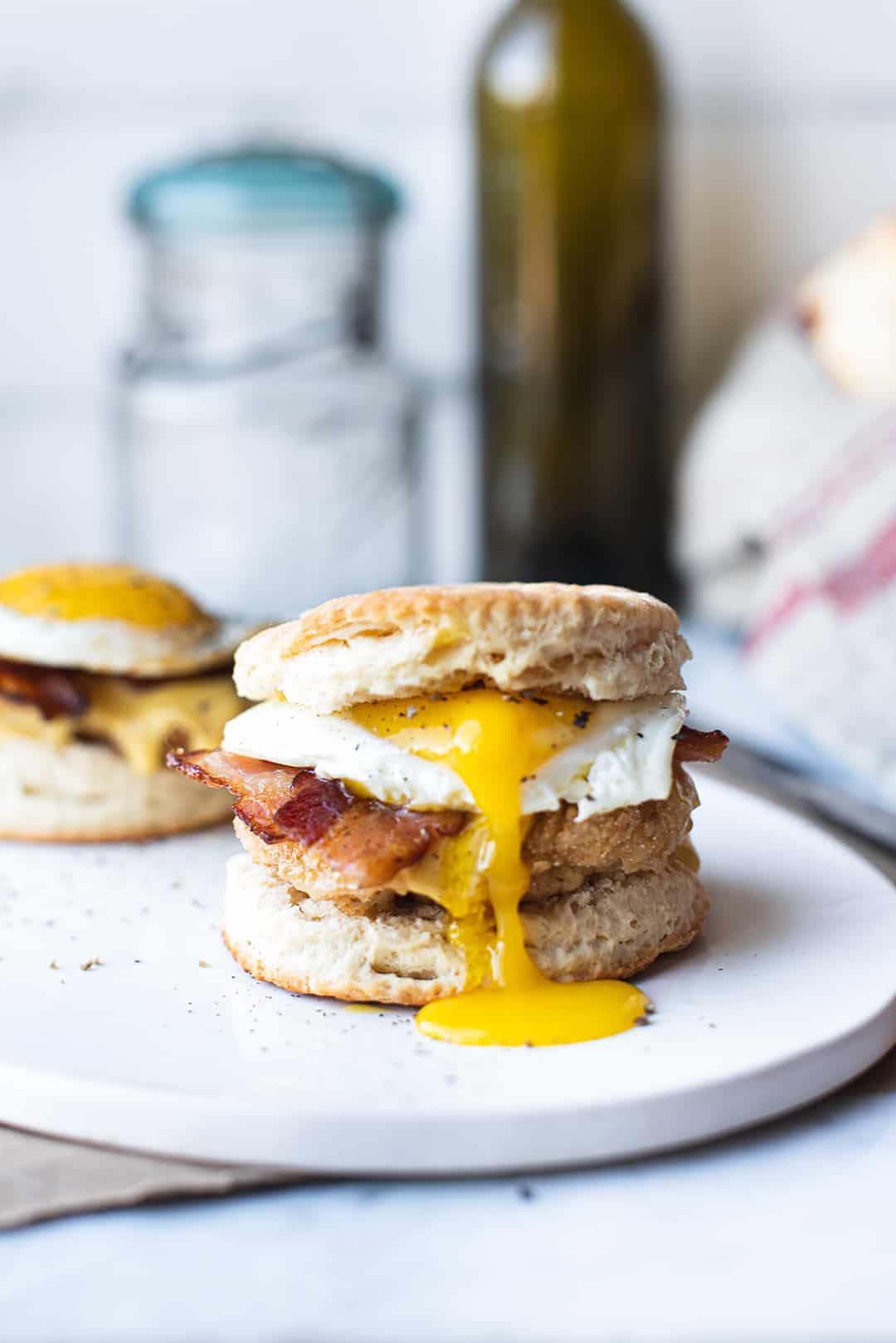 chicken & biscuit sandwich with runny yolk on white plate