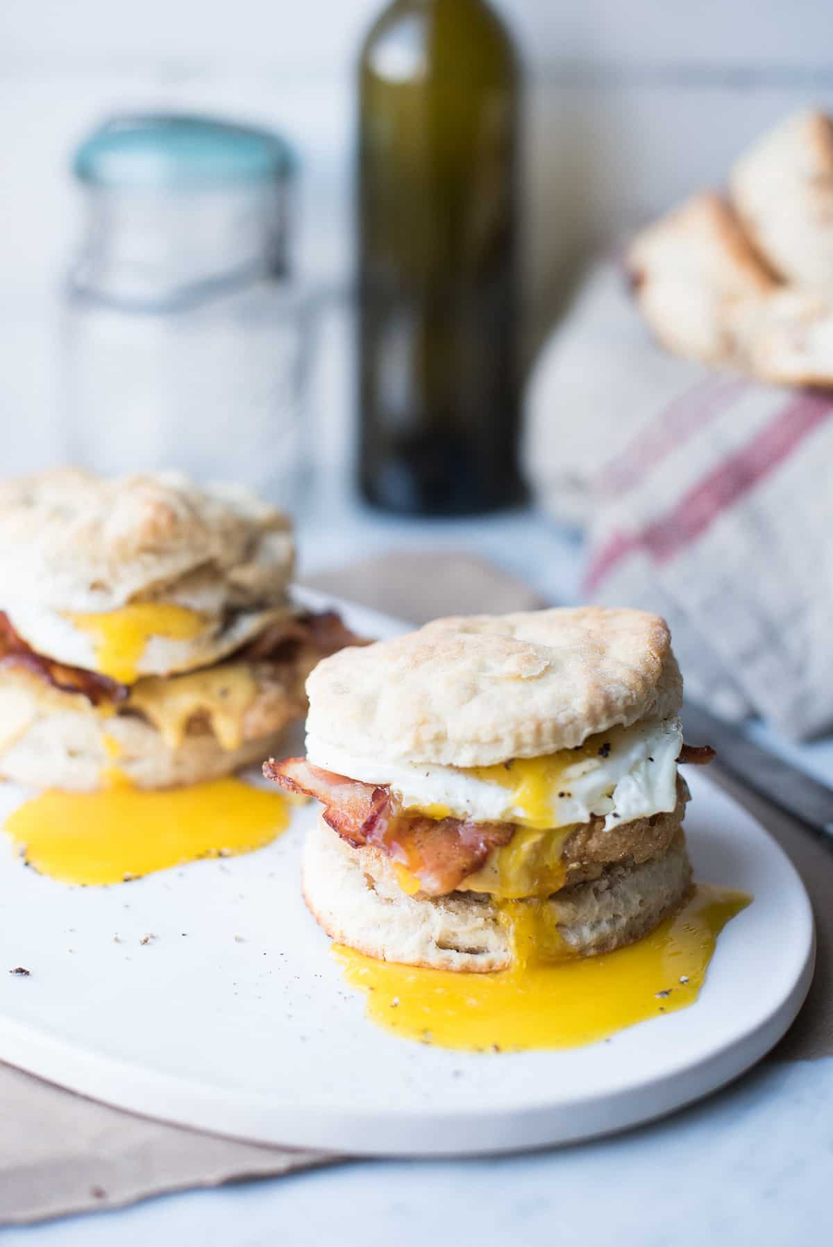 two biscuit sandwiches with runny yolks on white plate
