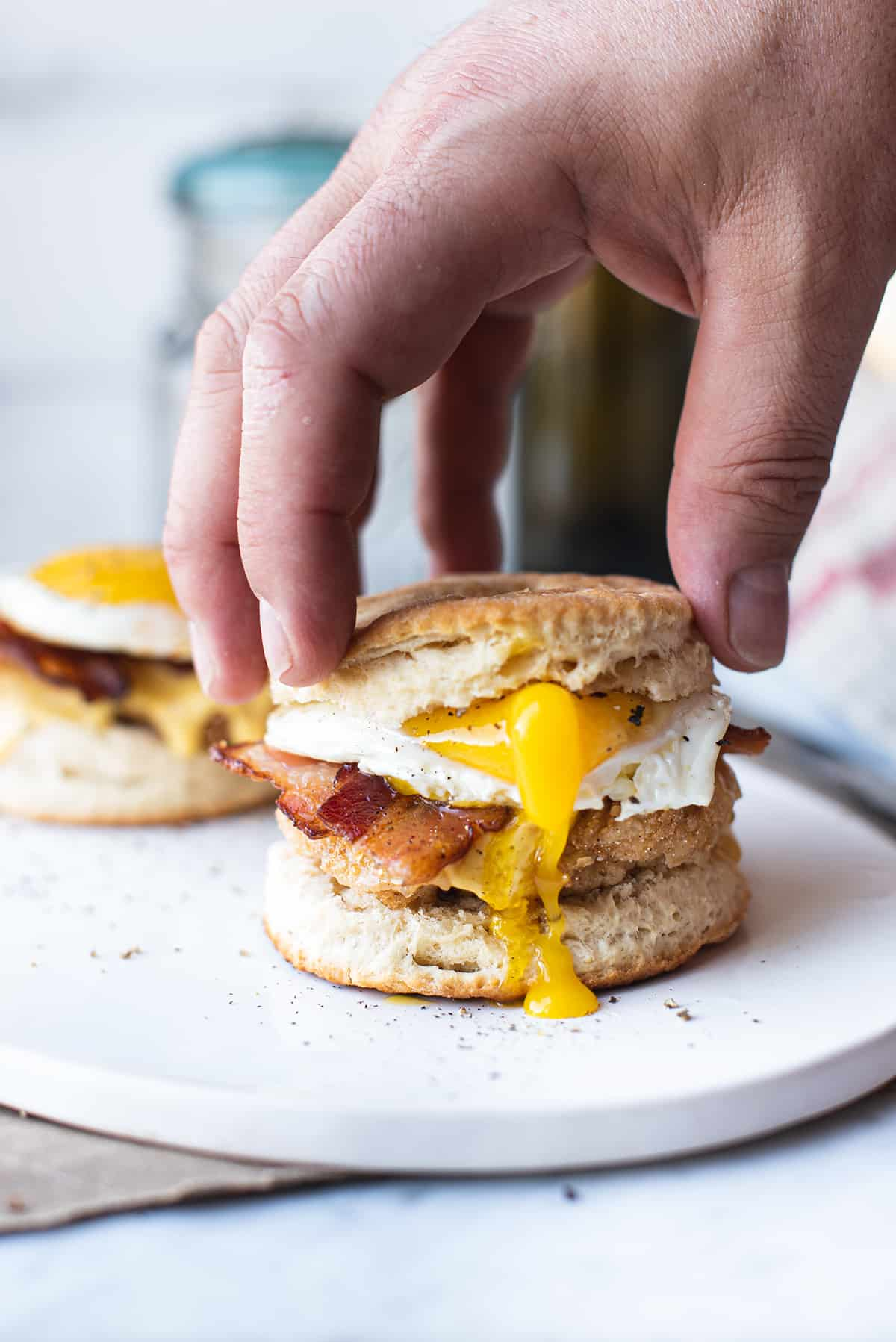 chicken & biscuit sandwich with hand on top and runny yolk