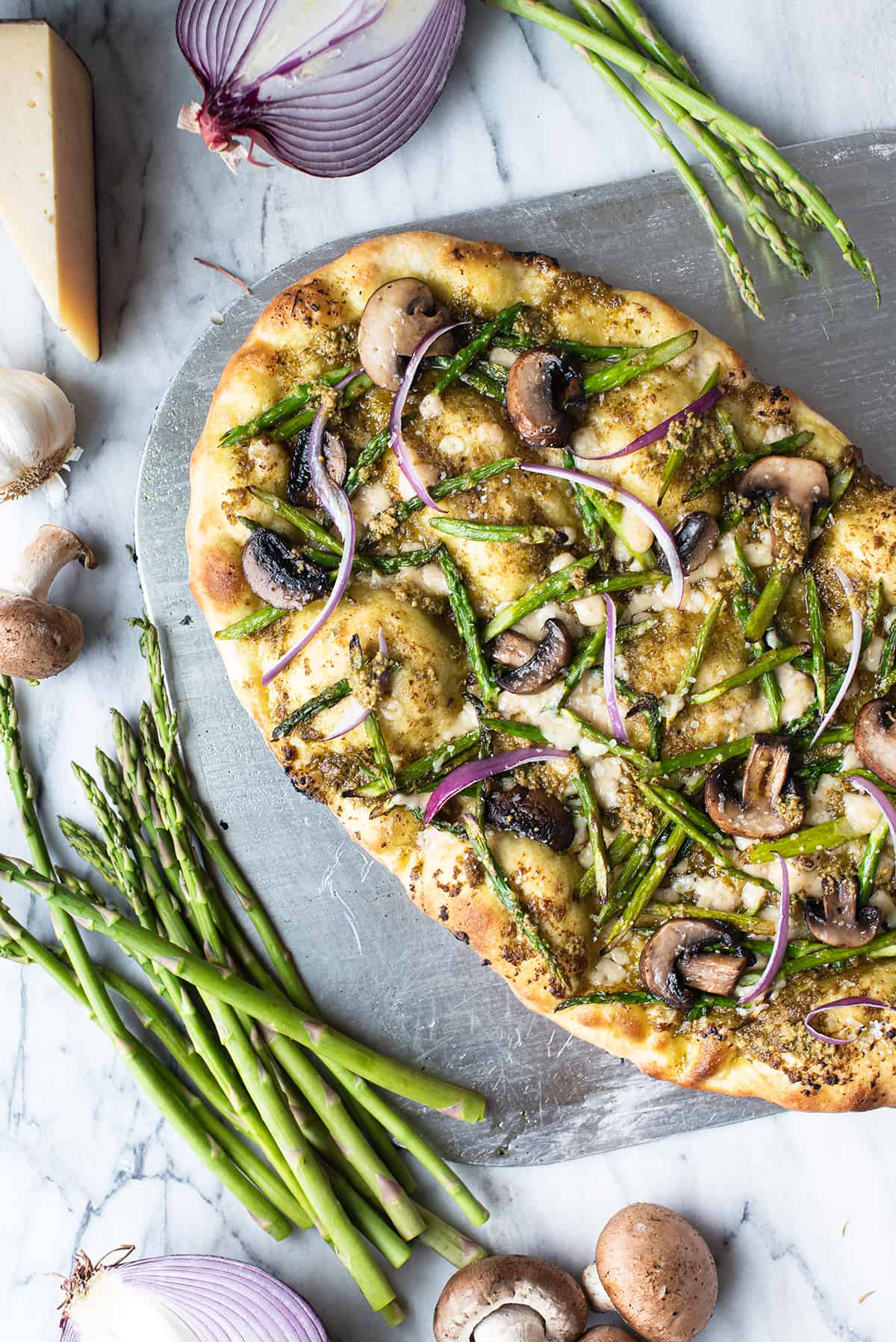 whole pizza on metal slab with asparagus spears