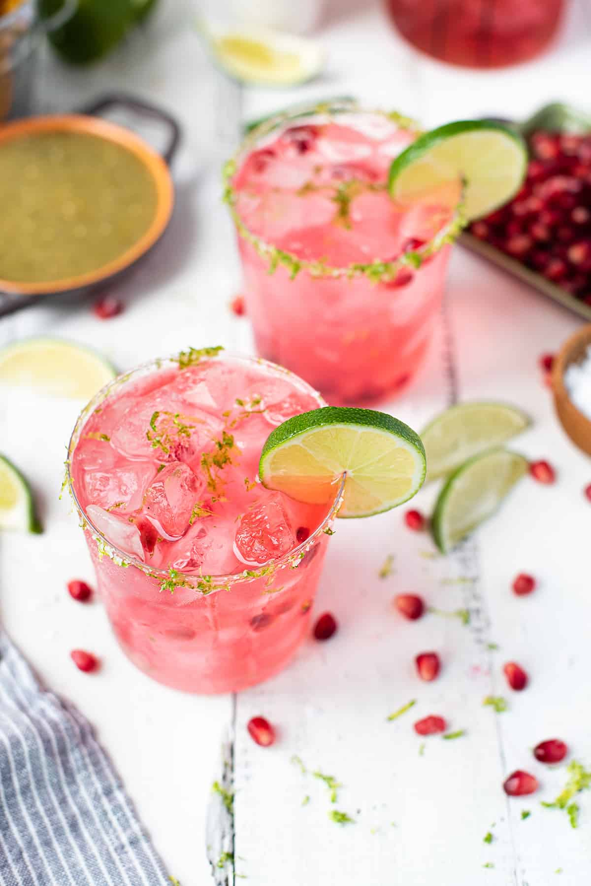 two pink pomegranate margaritas garnished with slice on white table