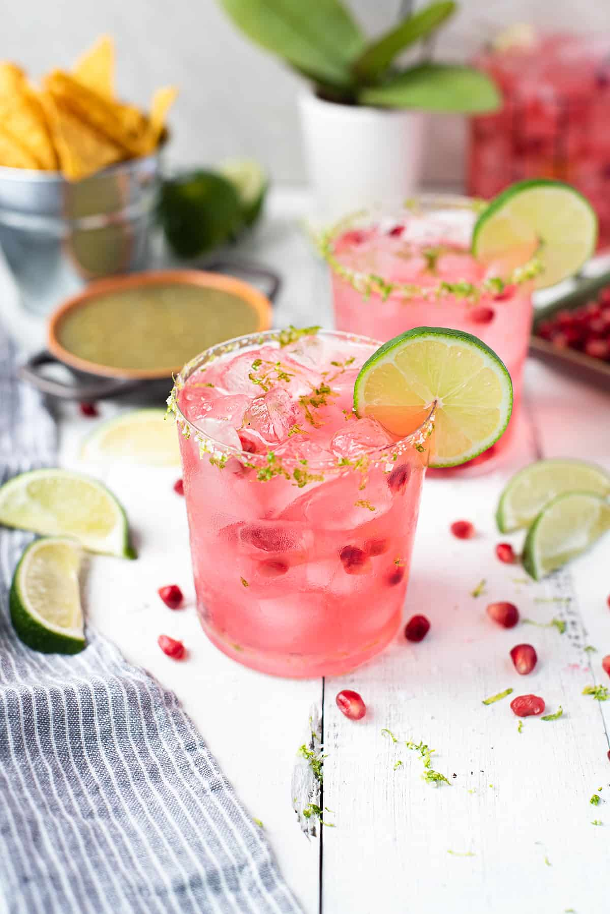 pink pomegranate margaritas with lime & salt rim & lime garnish on white table