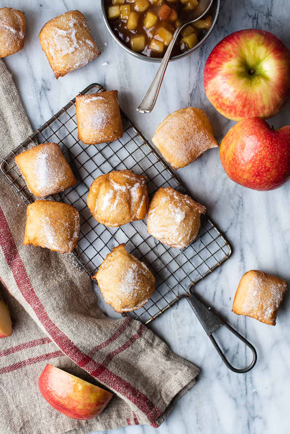 apple beignet bites on wire tray with linen napkin + apples