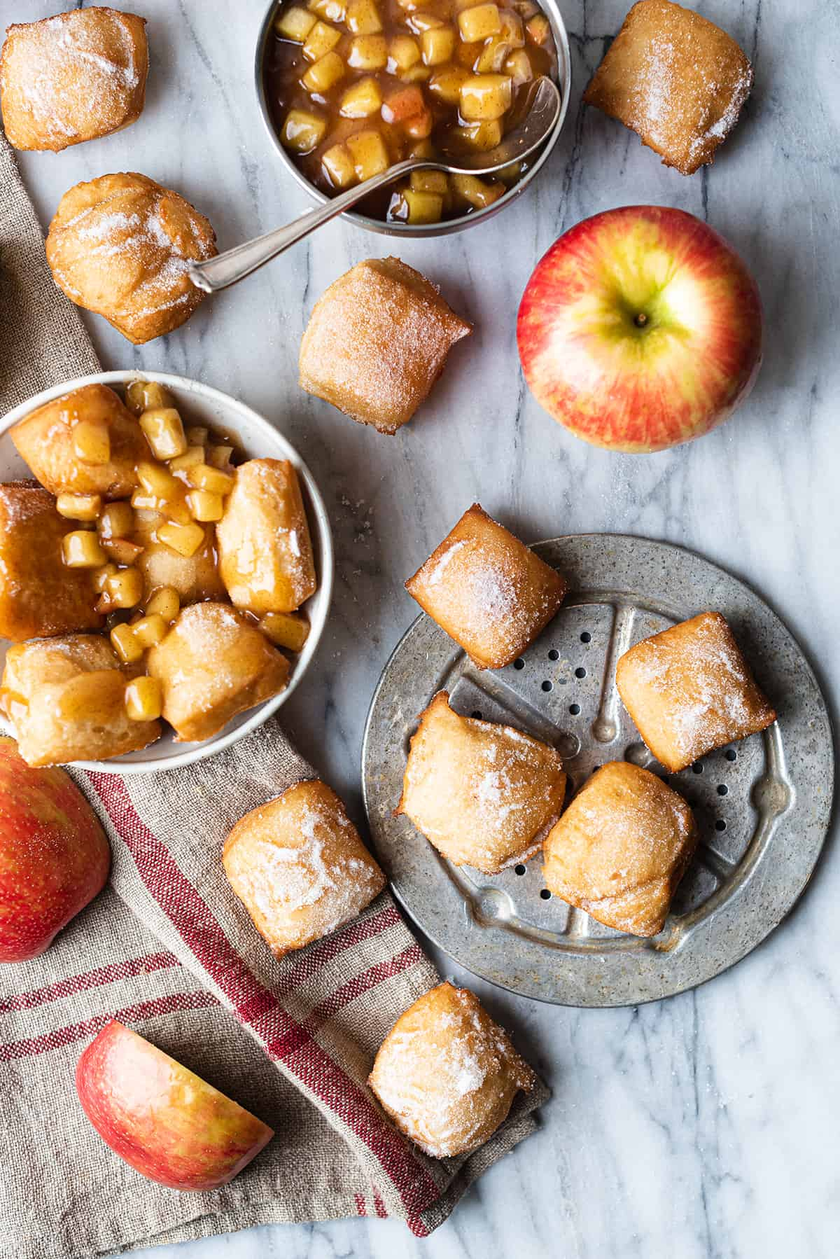 apple beignet bites on silver platter with bowl of apple compote + linen napkin, apples
