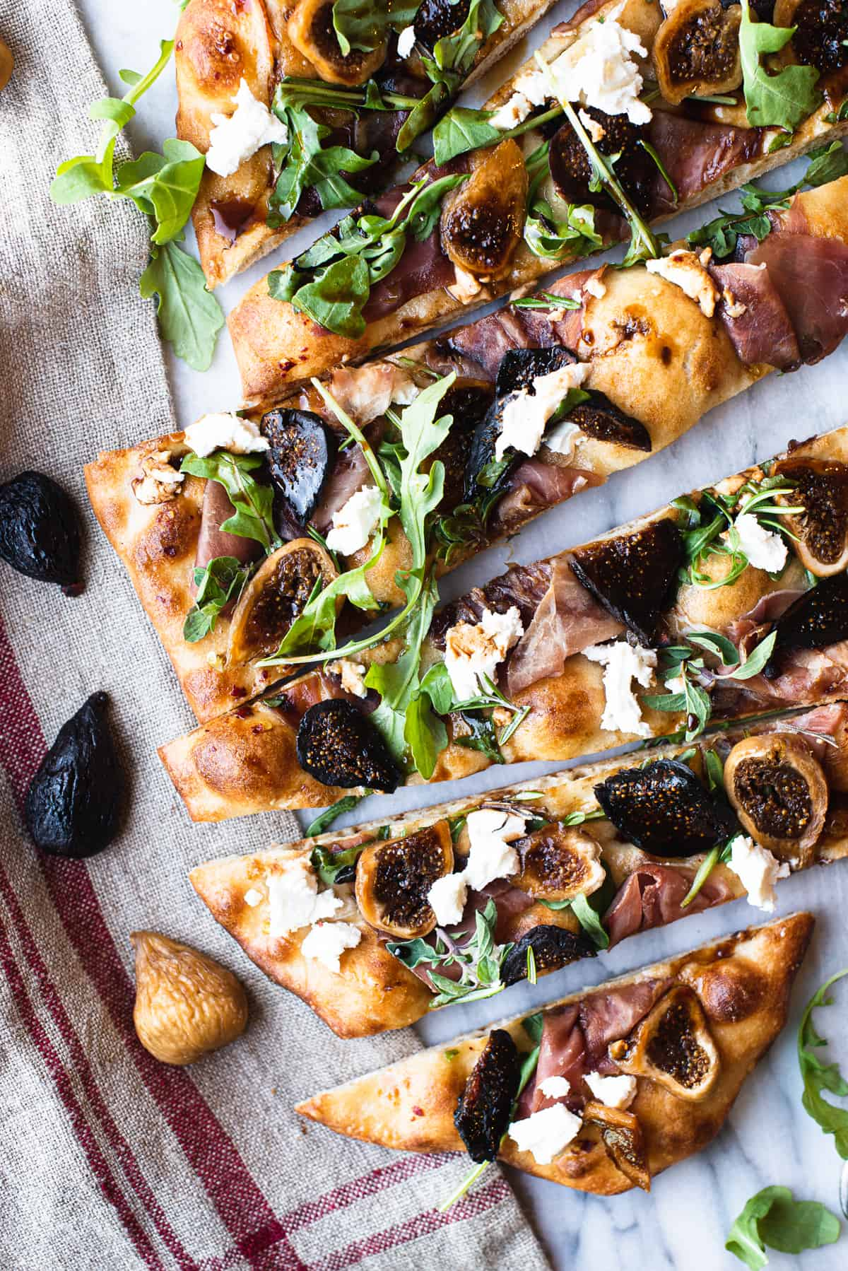 fig flatbread slices on white marble with knife & balsamic glaze