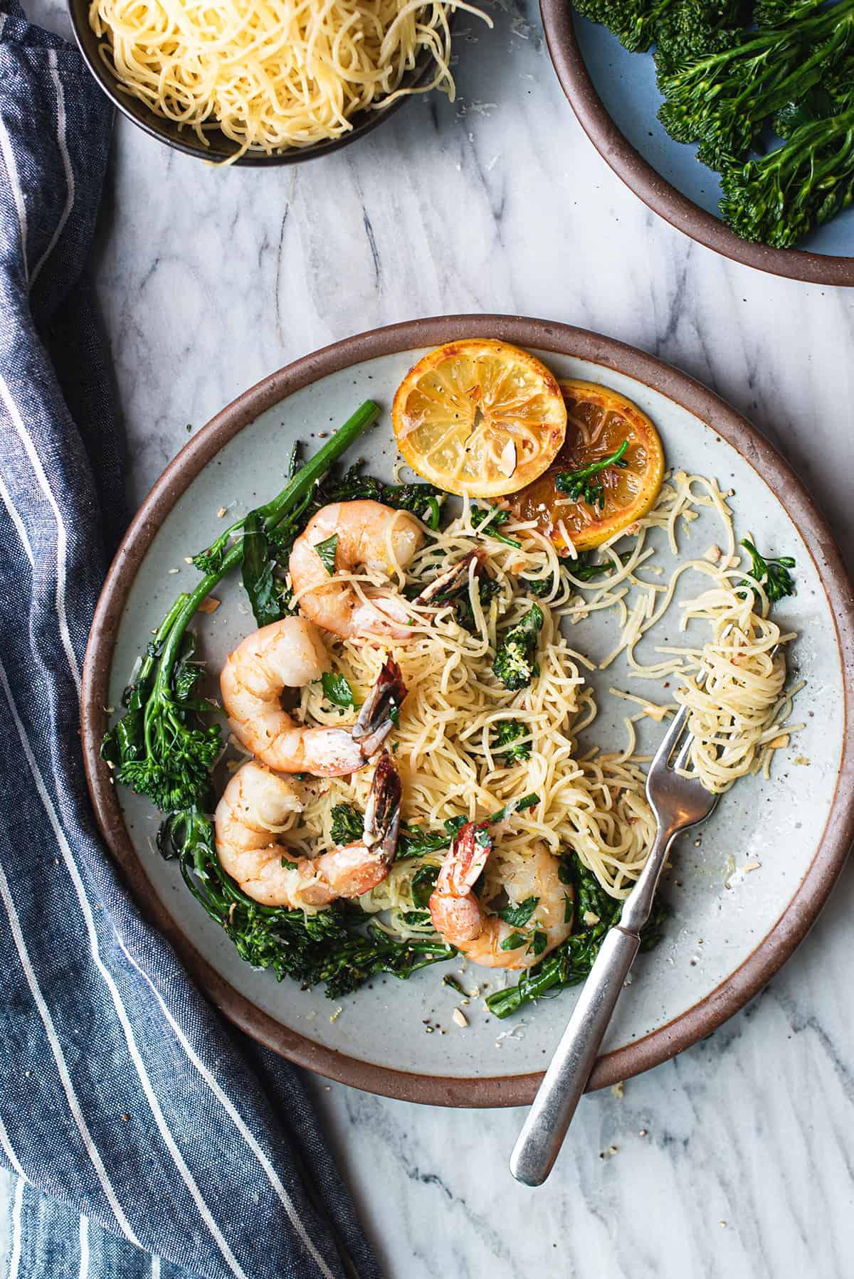 lemony shrimp pasta on white plate, twirled on fork + blue napkin