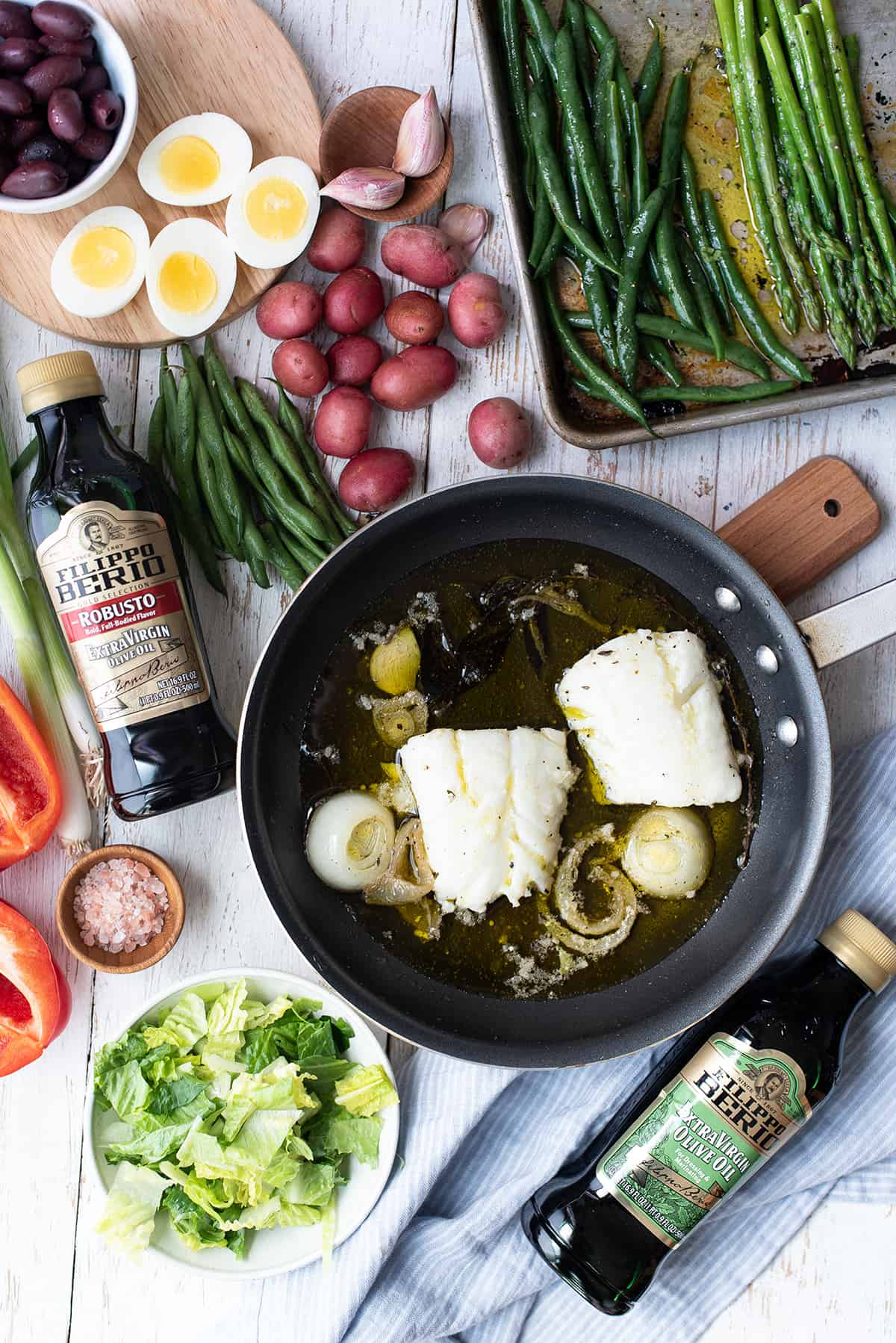 olive oil poached cod in pan + ingredients