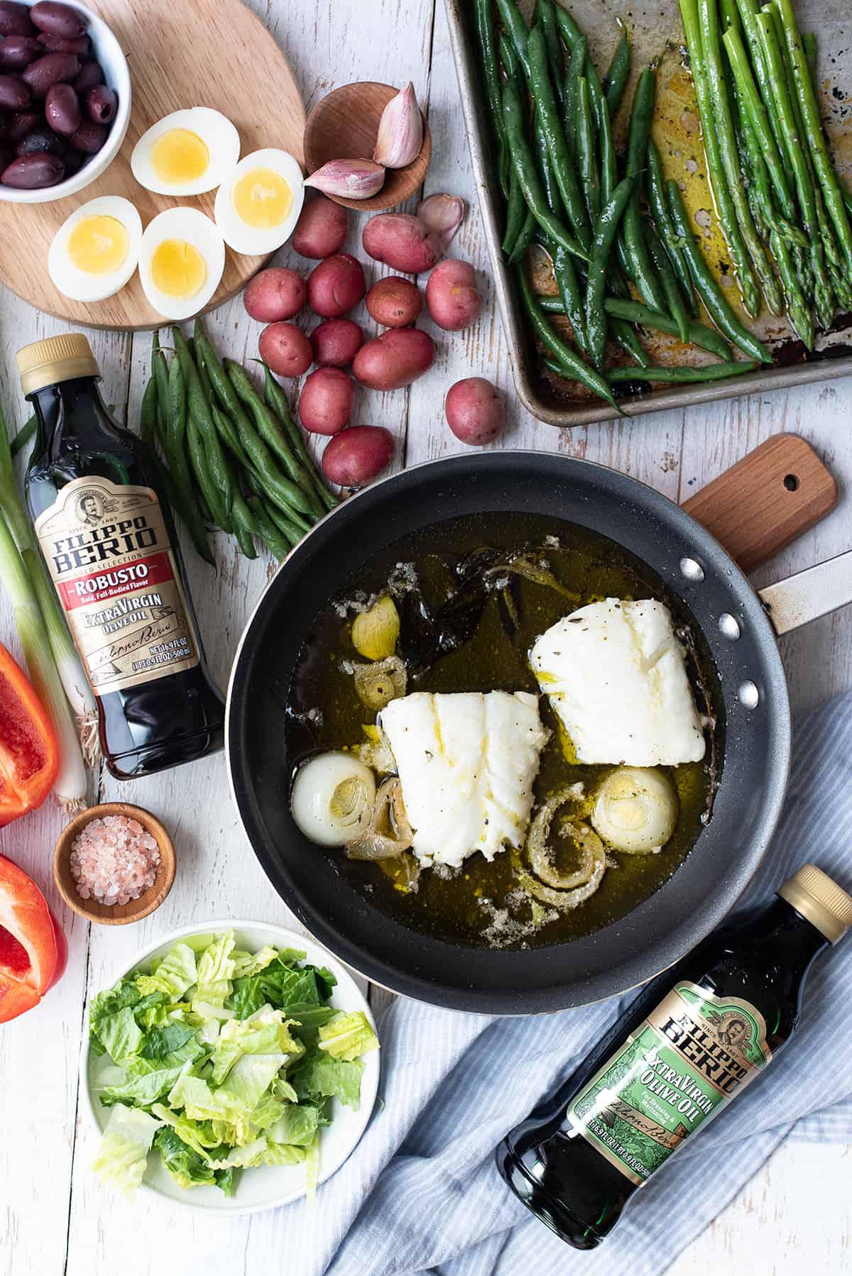 olive oil poached cod in pan + ingredients